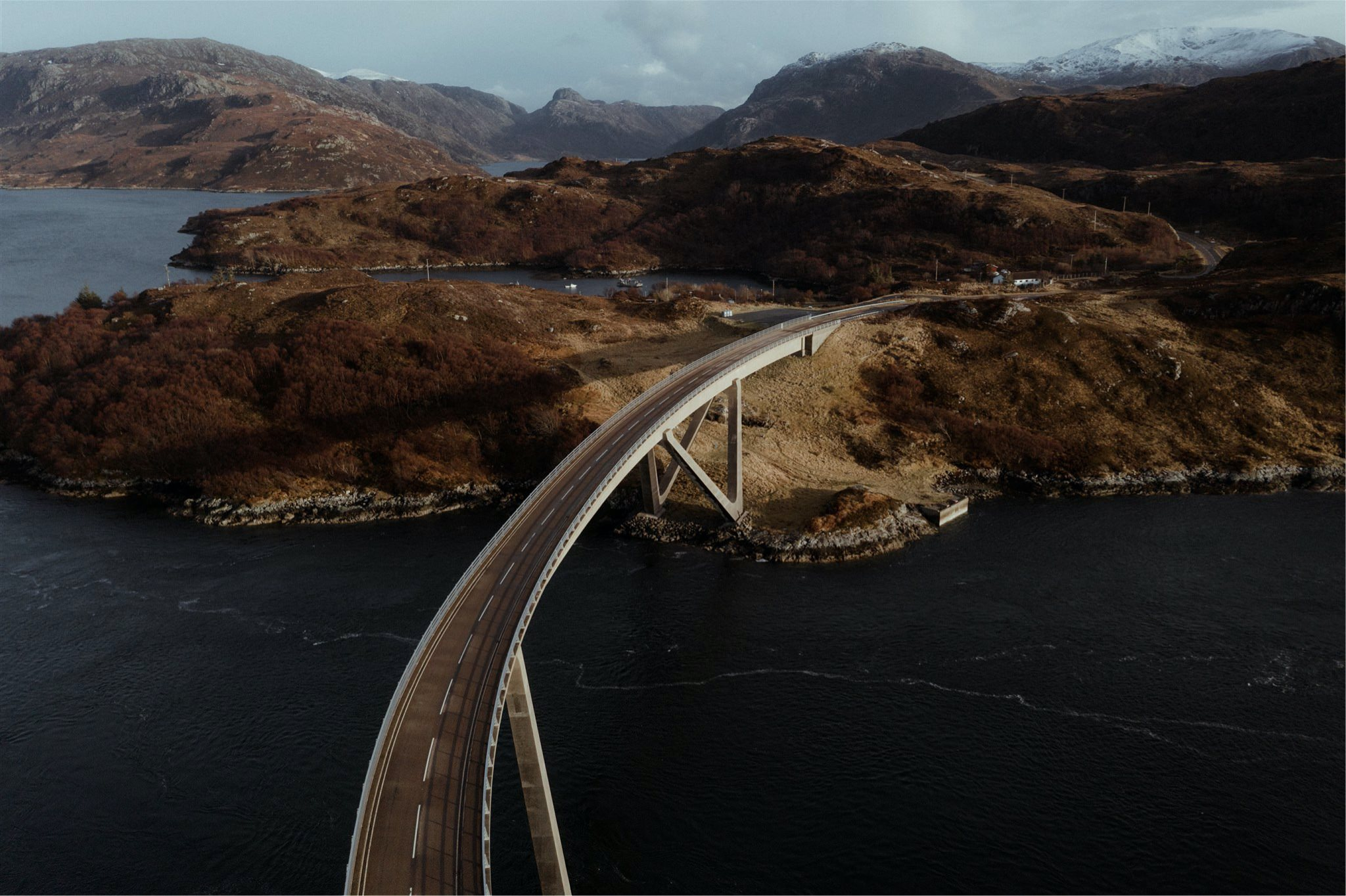 Drone shot of bridge with mountain backdrop in Assynt, Scotland