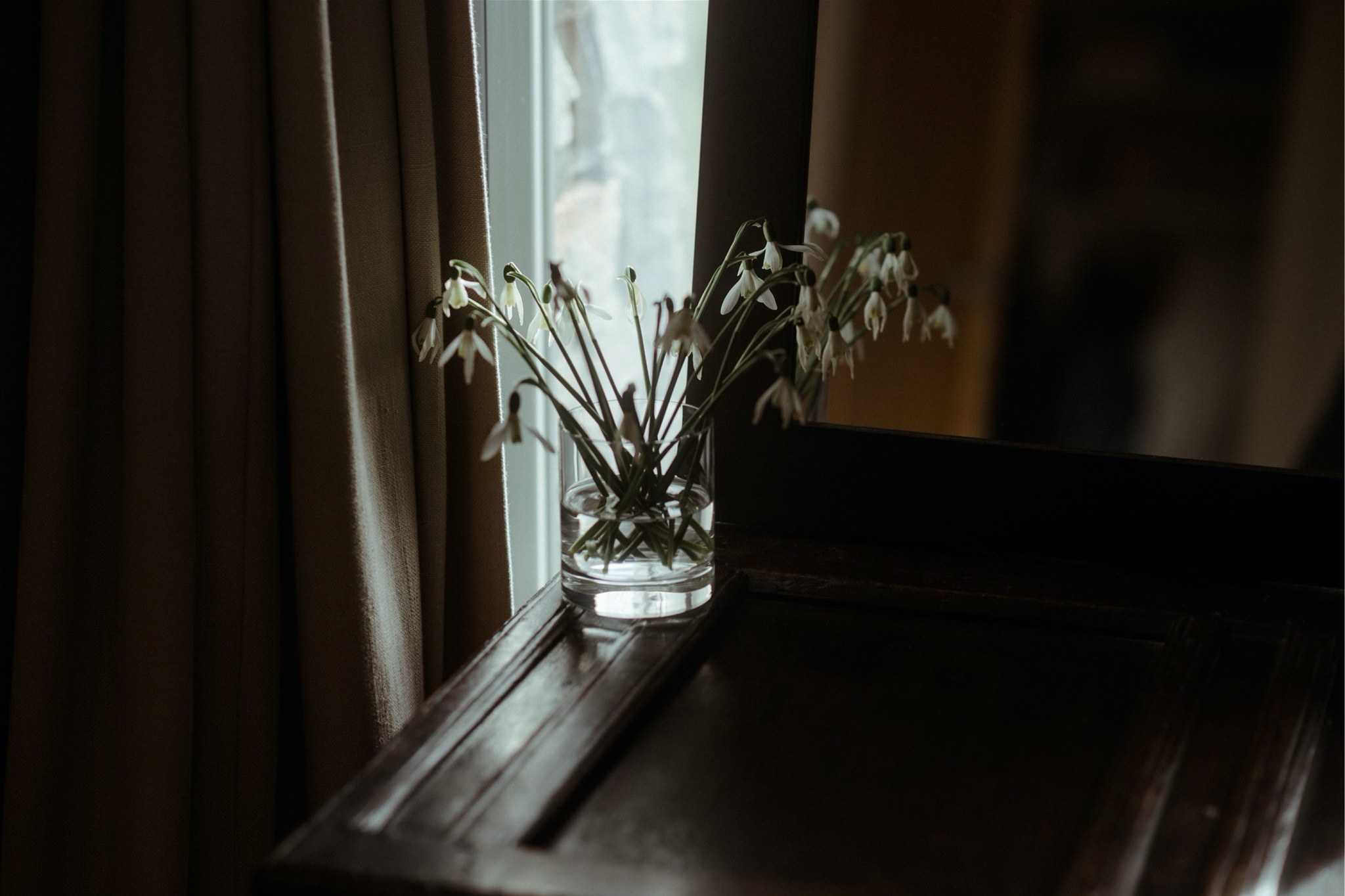 Snowdrops in a glass on a dresser
