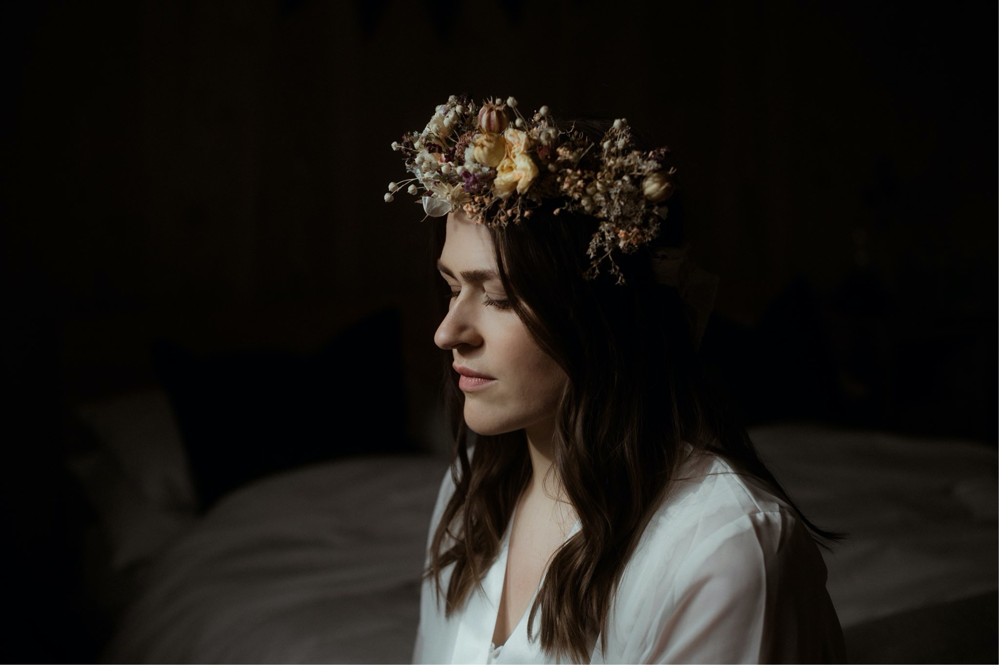 Bride with flower crown against a dark backdrop at a Scottish elopement wedding