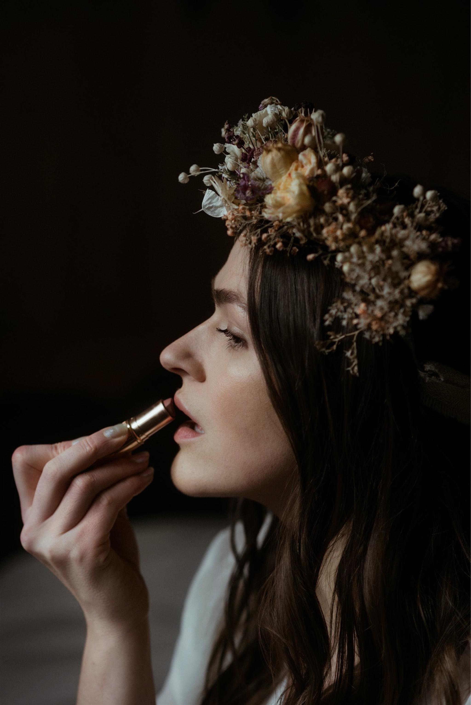 Bride with flower crown applies lipstick at her elopement wedding in Scotland