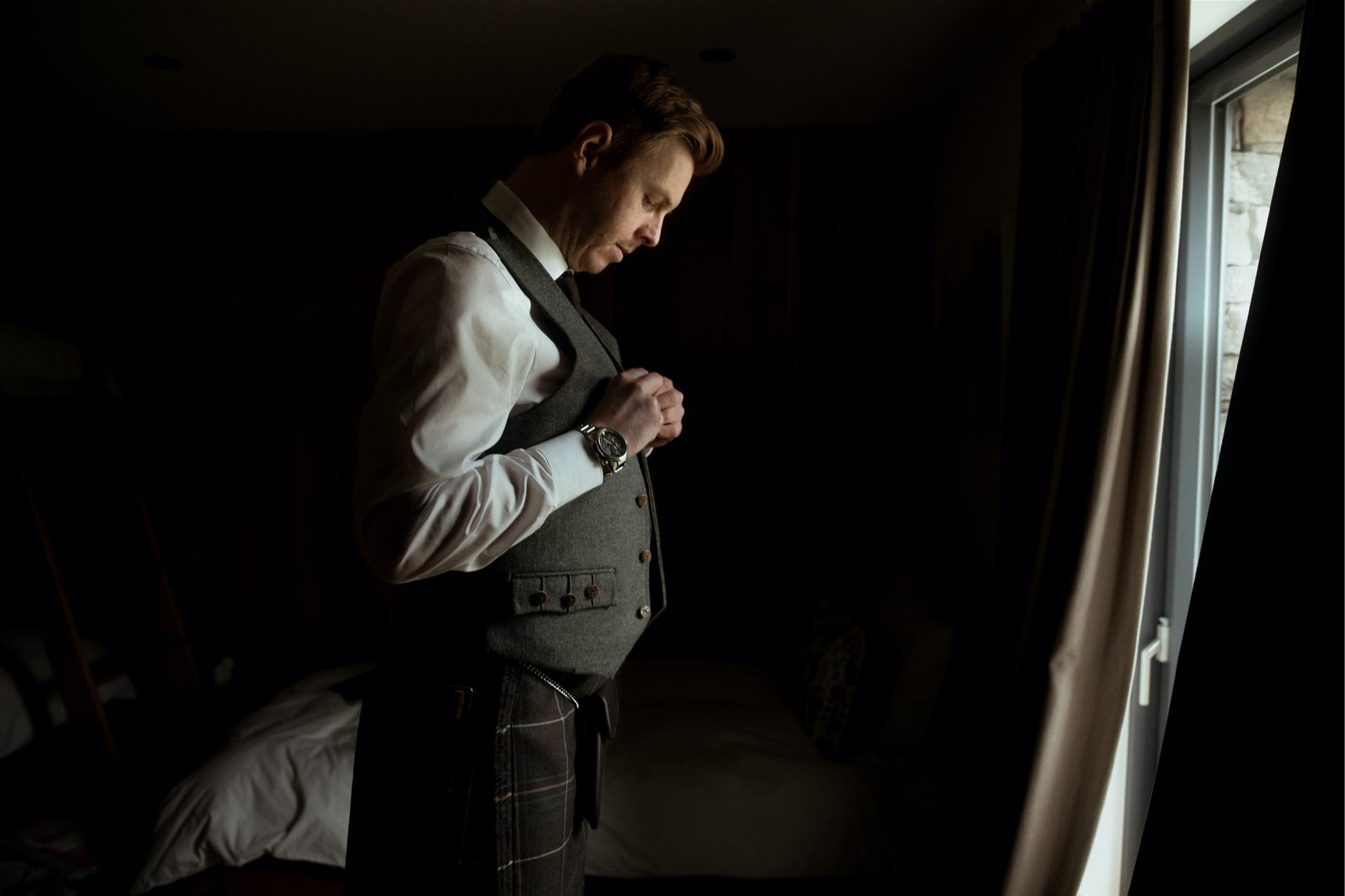 Groom doing up his waistcoat getting ready for his elopement in Scotland