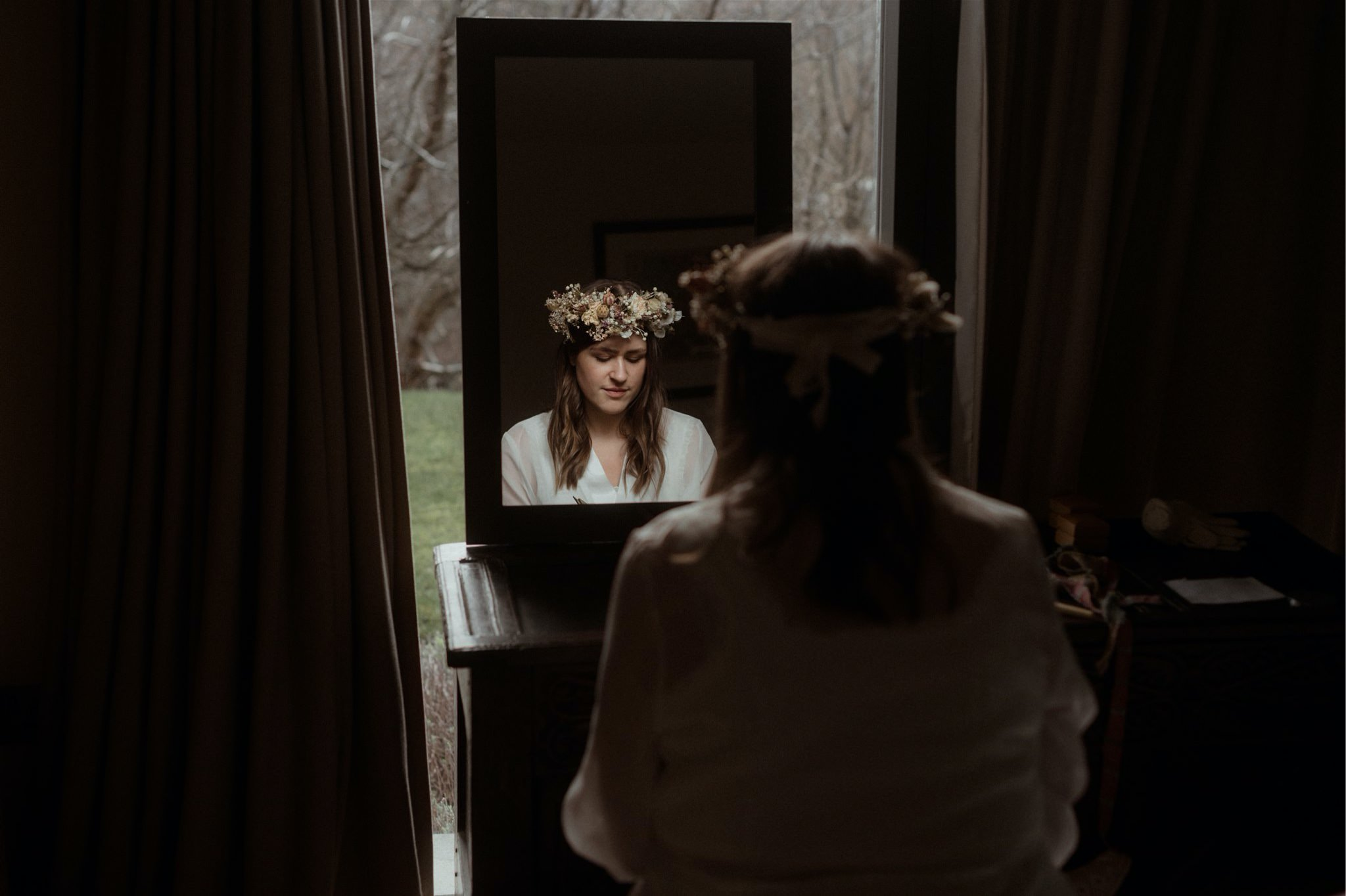 Bride with flower crown in front of a mirror at an elopement in Scotland