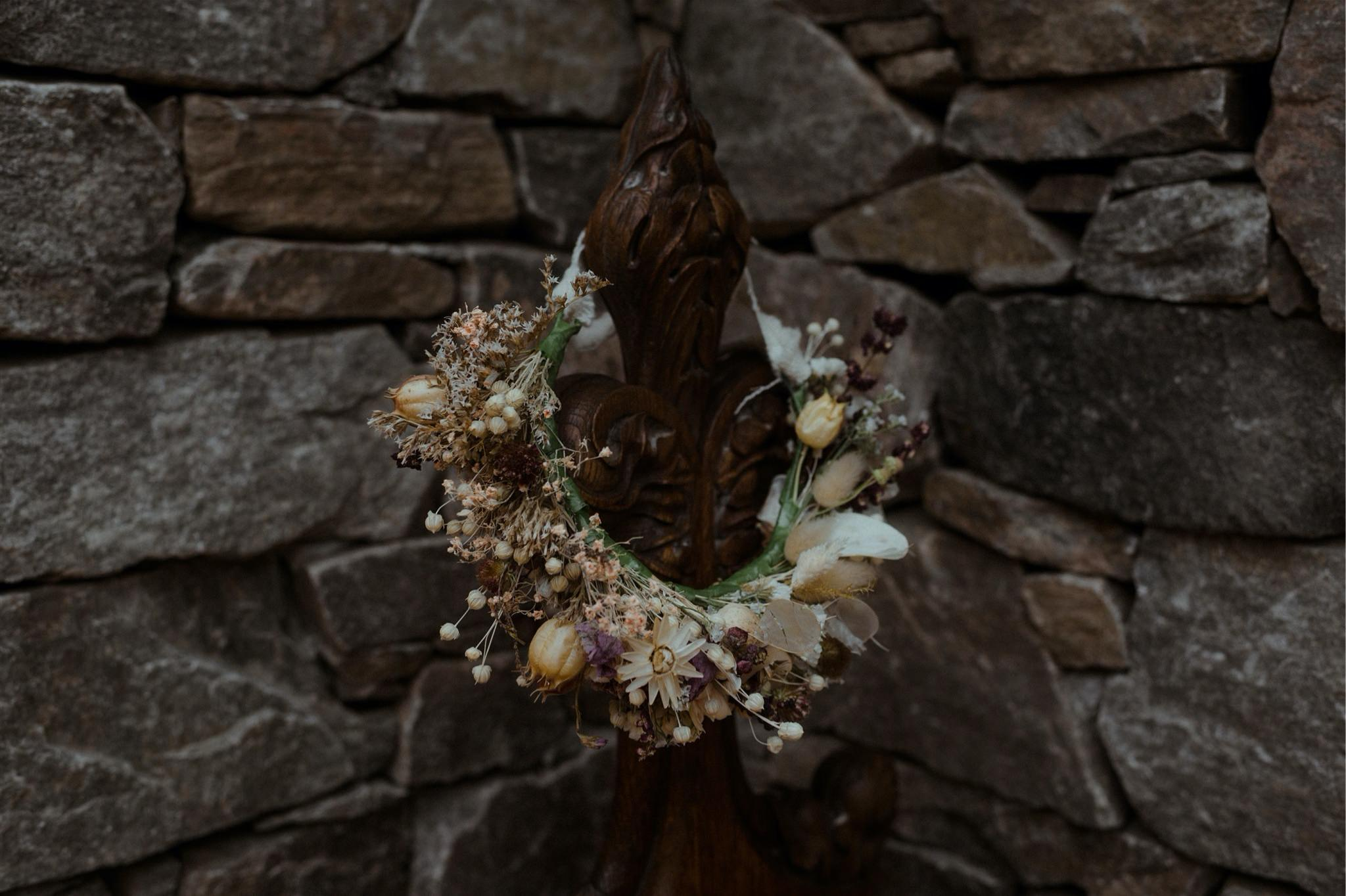 Details shot of flower crown against stone wall at a Scottish elopement