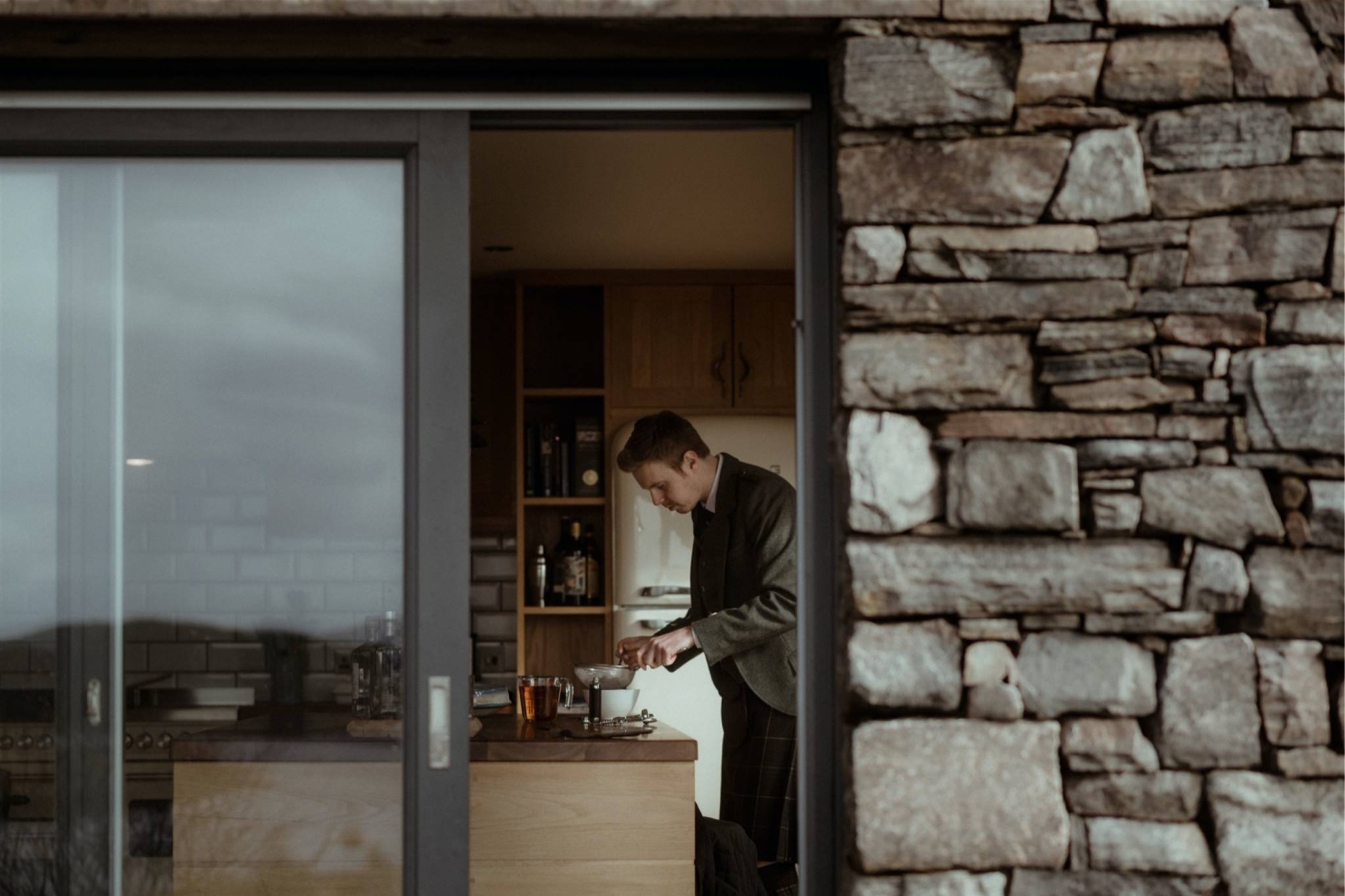 Shot of groom through open window in kitchen of his Scottish elopement accommodation
