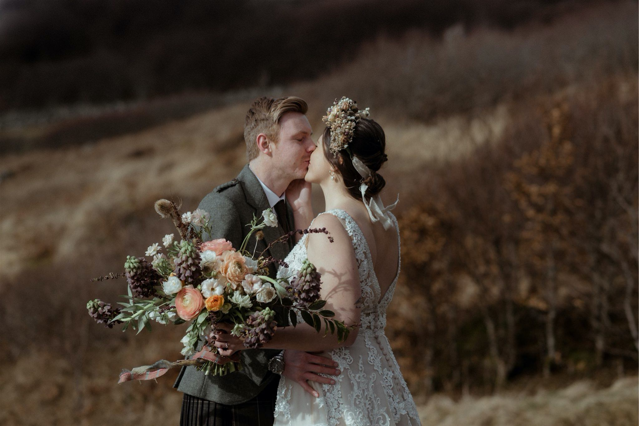 Bride with flower bouquet and groom kiss during their elopement wedding in Assynt, Scotland