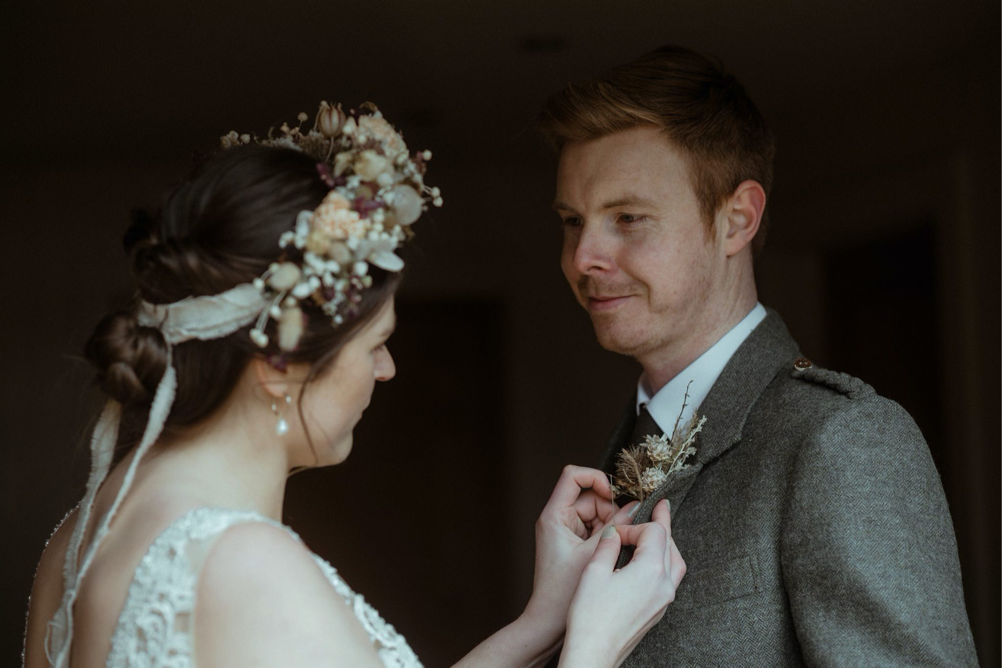 Bride attaches groom's buttonhole during their Assynt elopement in Scotland