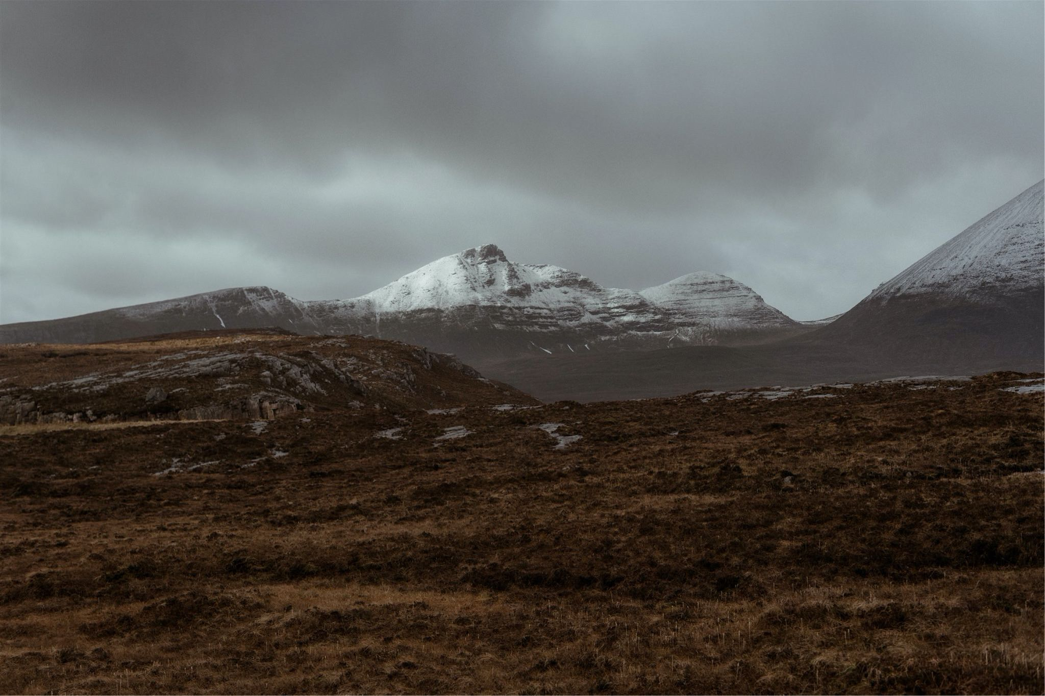 View of snowcapped mountains and moorland in Assynt, Scotland