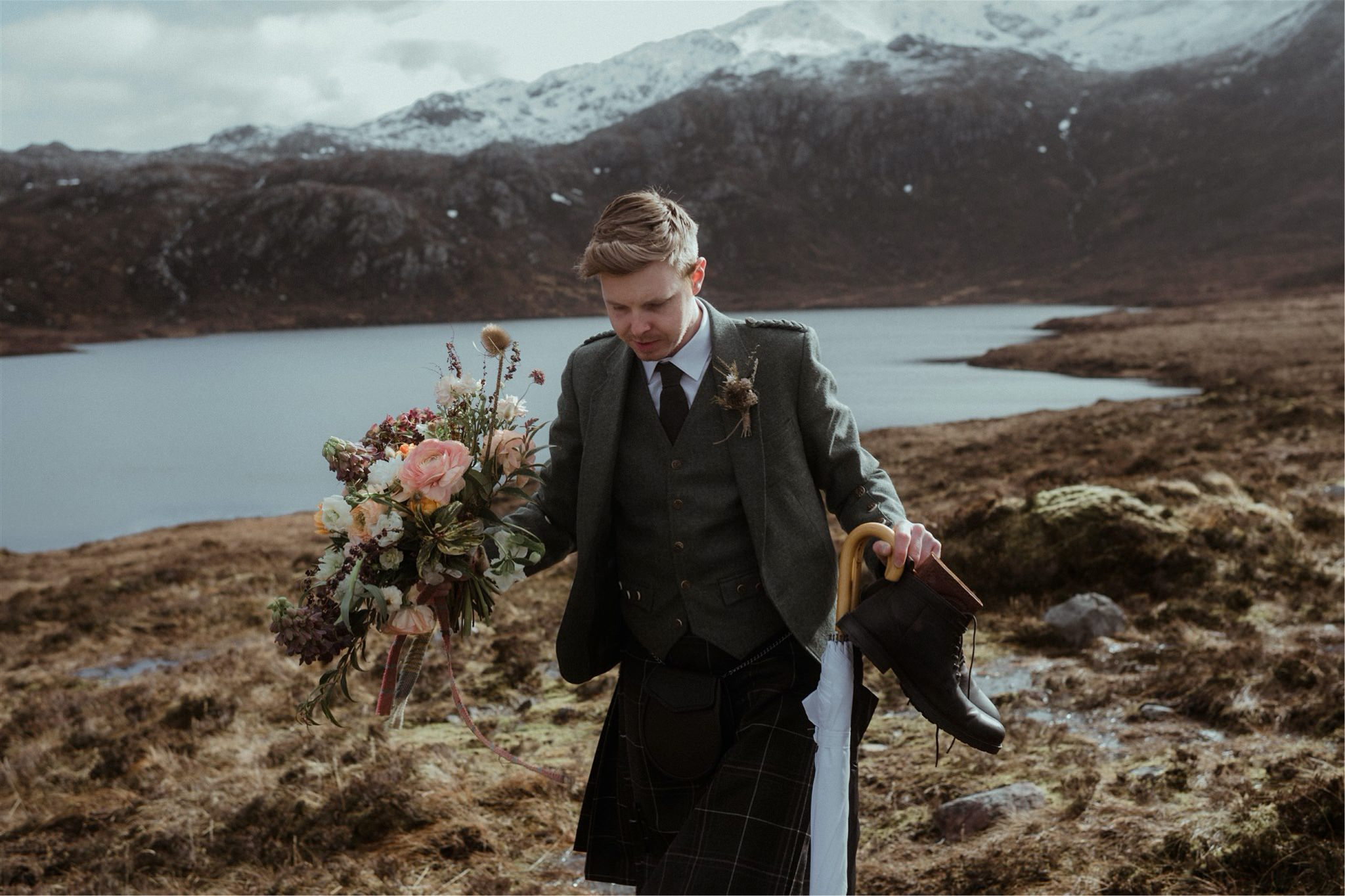 Groom carrying flowers, boots and umbrellas at an elopement in Assynt, Scotland