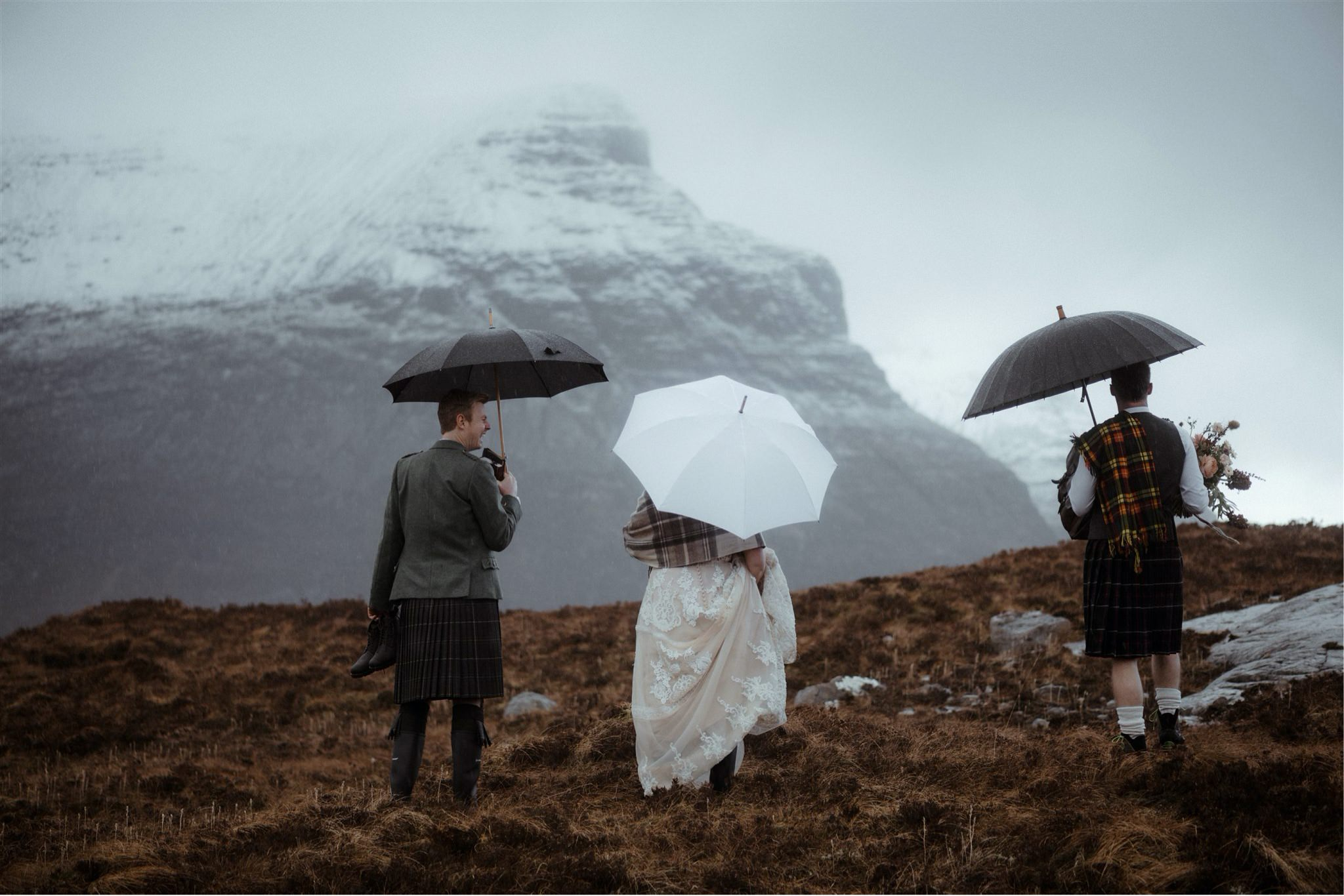 Bride, groom and celebrant with umbrellas at an elopement wedding in Assynt, Scotland