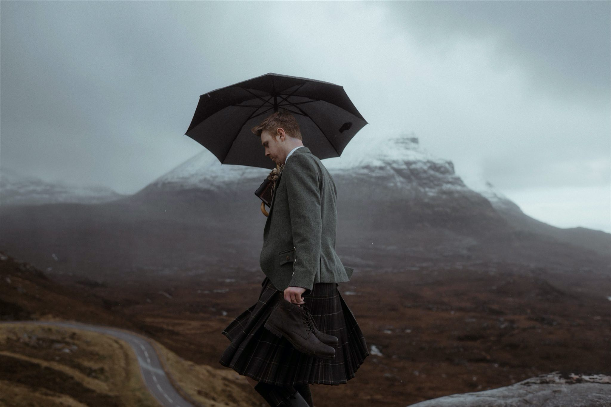 Groom in a kilt with an umbrella arrives for his Scotland elopement in Assynt