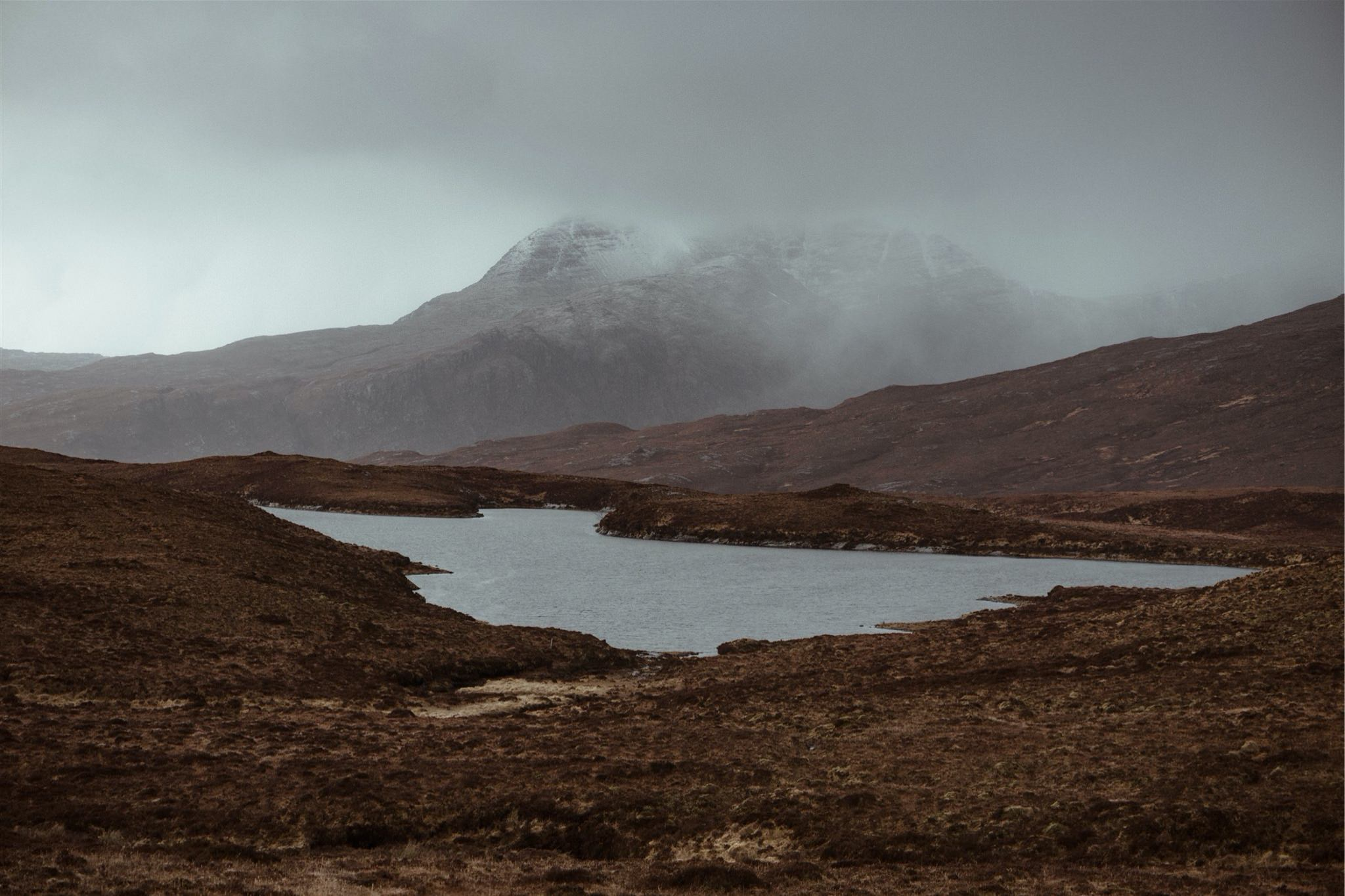 View of a loch an with misty mountains behind in Assynt, Scotland