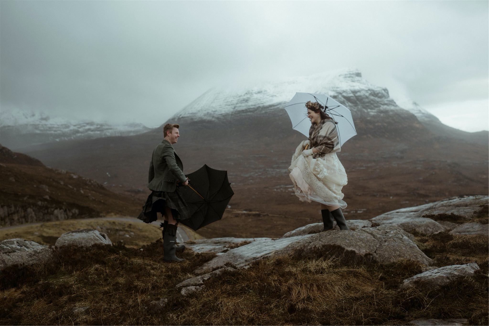 Bride and groom with umbrellas and mountain backdrop laughing at their Assynt elopement in Scotland