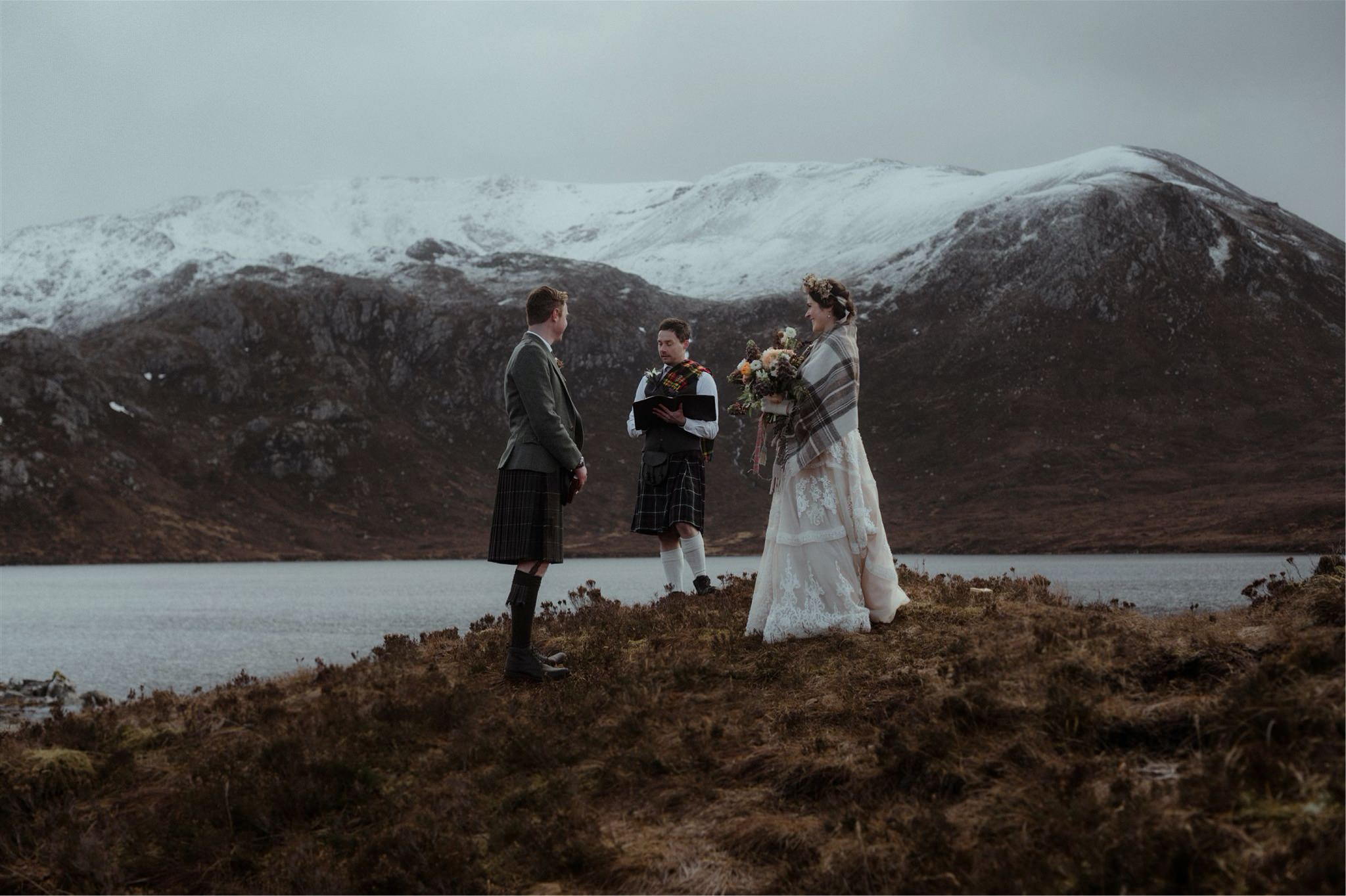 Scotland elopement wedding ceremony taking place by a loch and mountains in Assynt
