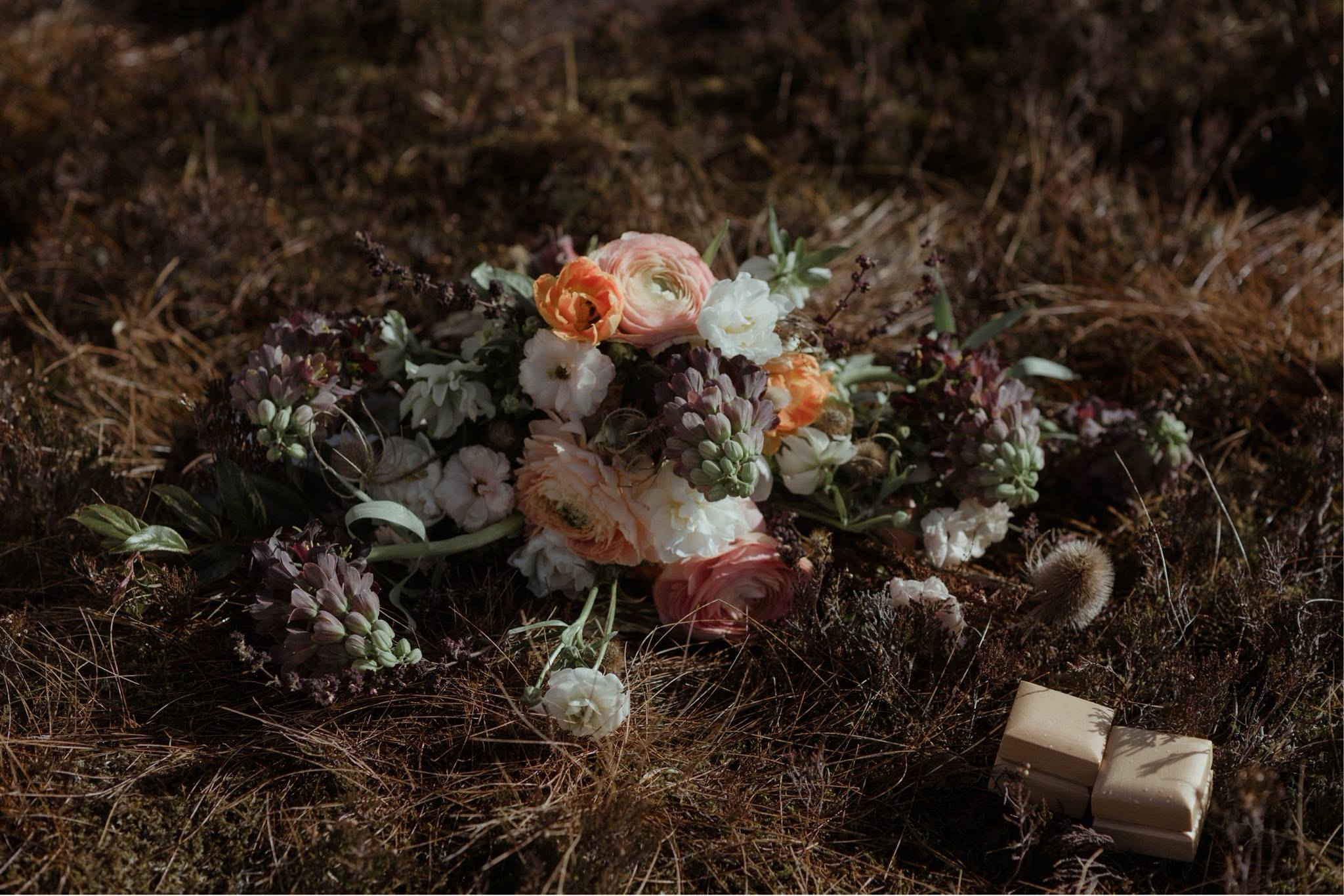Detail shot of bouquet and rings on the grass during a Scottish elopement wedding