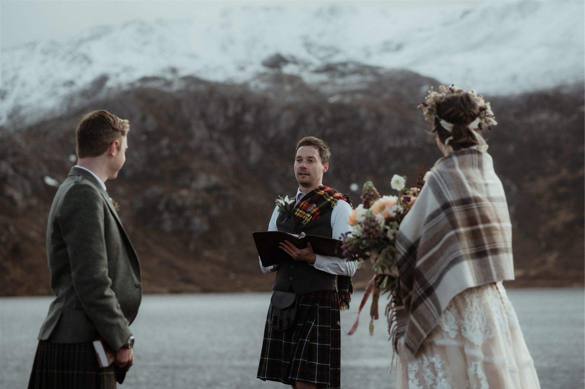 Bride, groom and celebrant with mountain backdrop at an elopement wedding in Assynt, Scotland