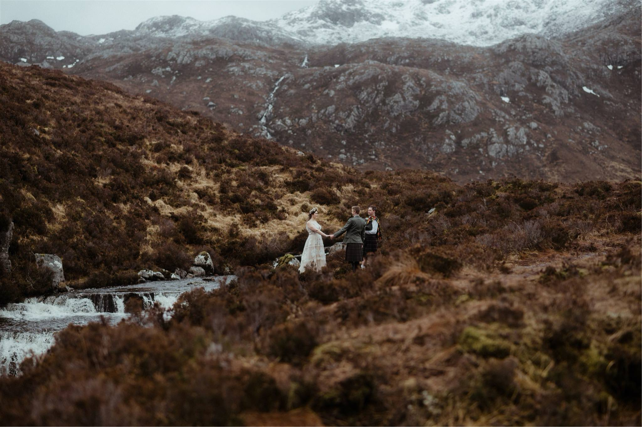 Bride and groom holding hands during their outdoor elopement wedding ceremony in the mountains of Scotland