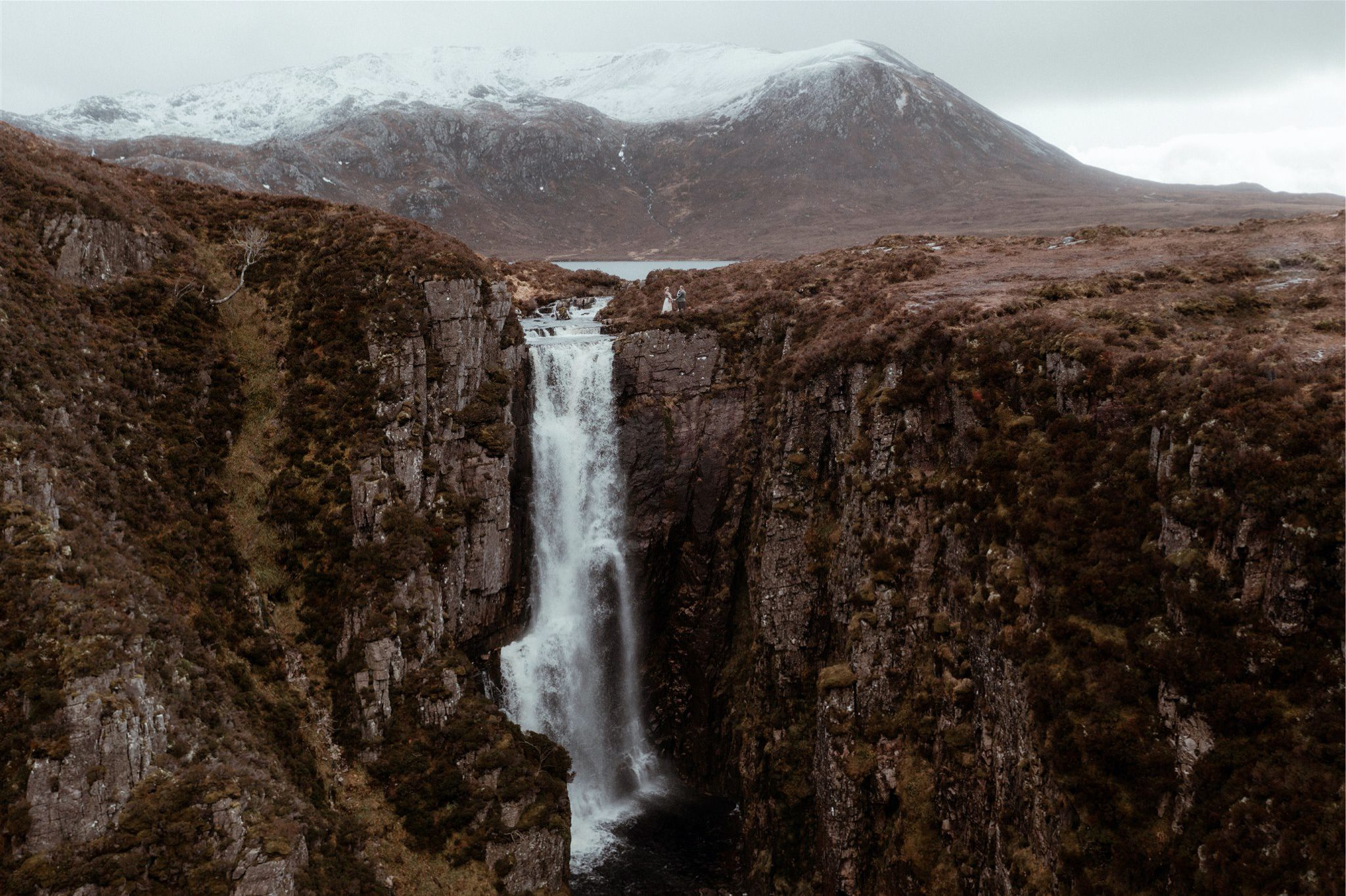 Wide shot of bride and groom holding hands during their Scotland elopement wedding in the mountains of Assynt