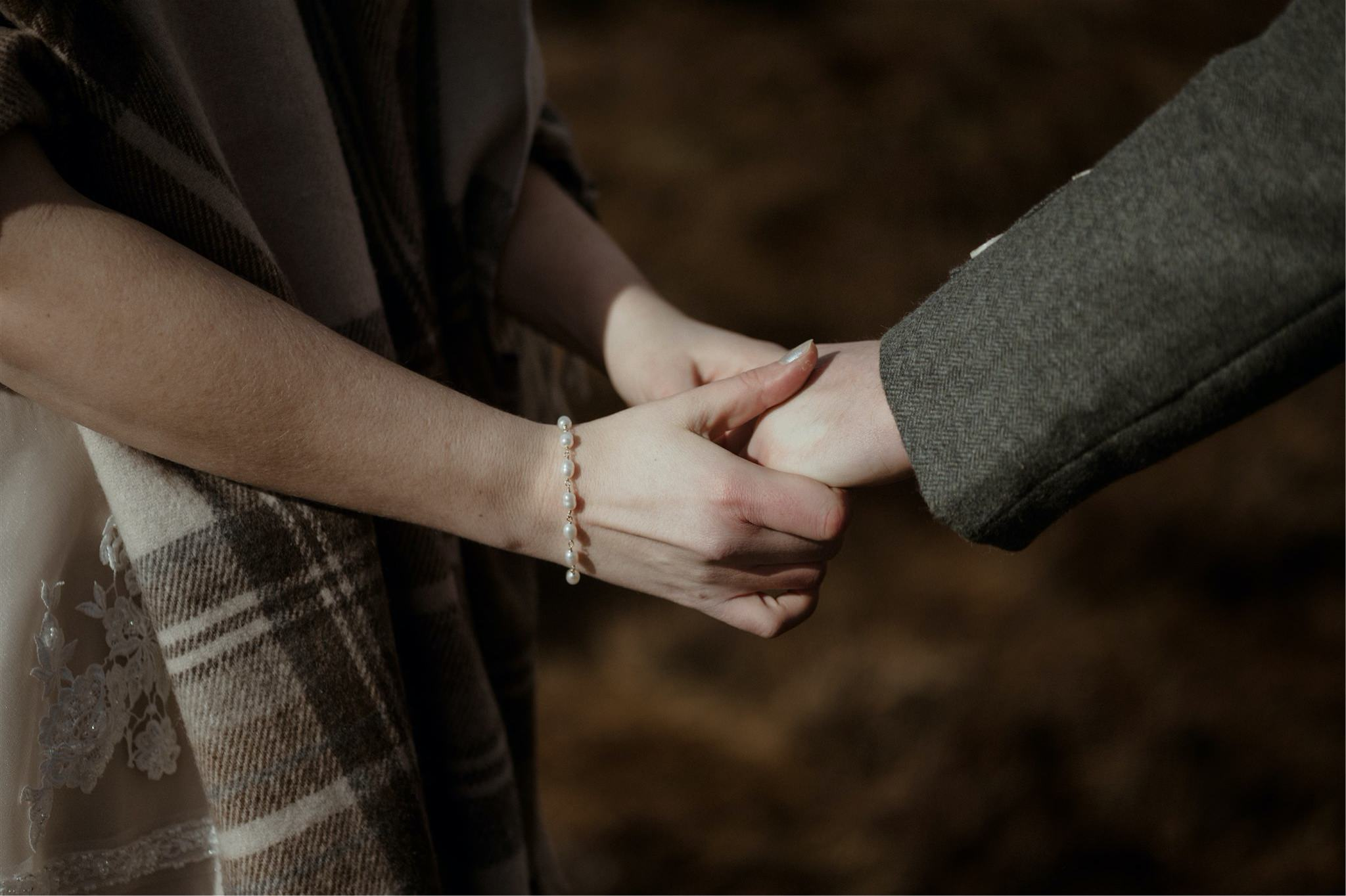 Detail shot of couple holding hands during a Scotland elopement wedding in Assynt