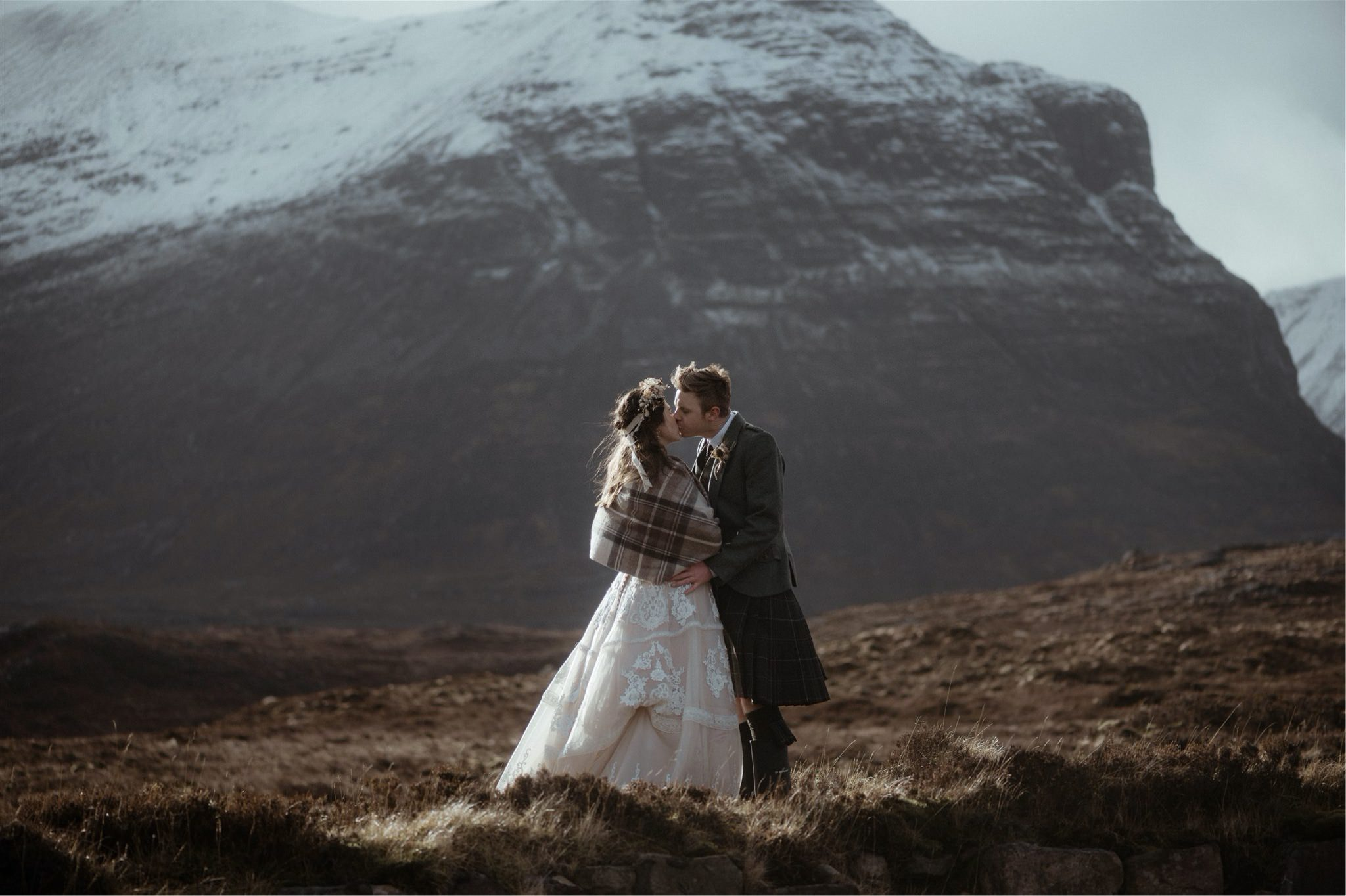 Couple kiss in front of mountain backdrop after their elopement wedding in Assynt, Scotland