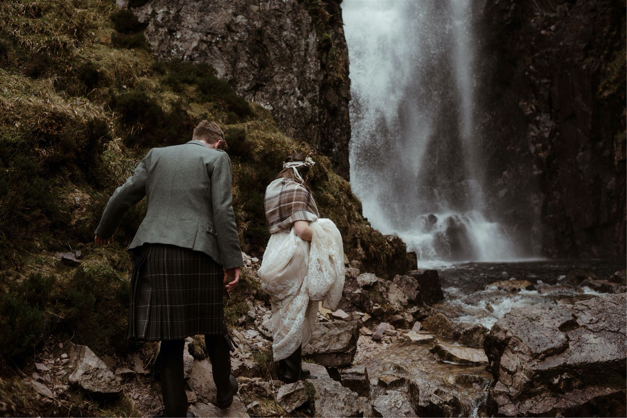 Bride and groom walking through a gorge after their Scotland elopement wedding in Assynt