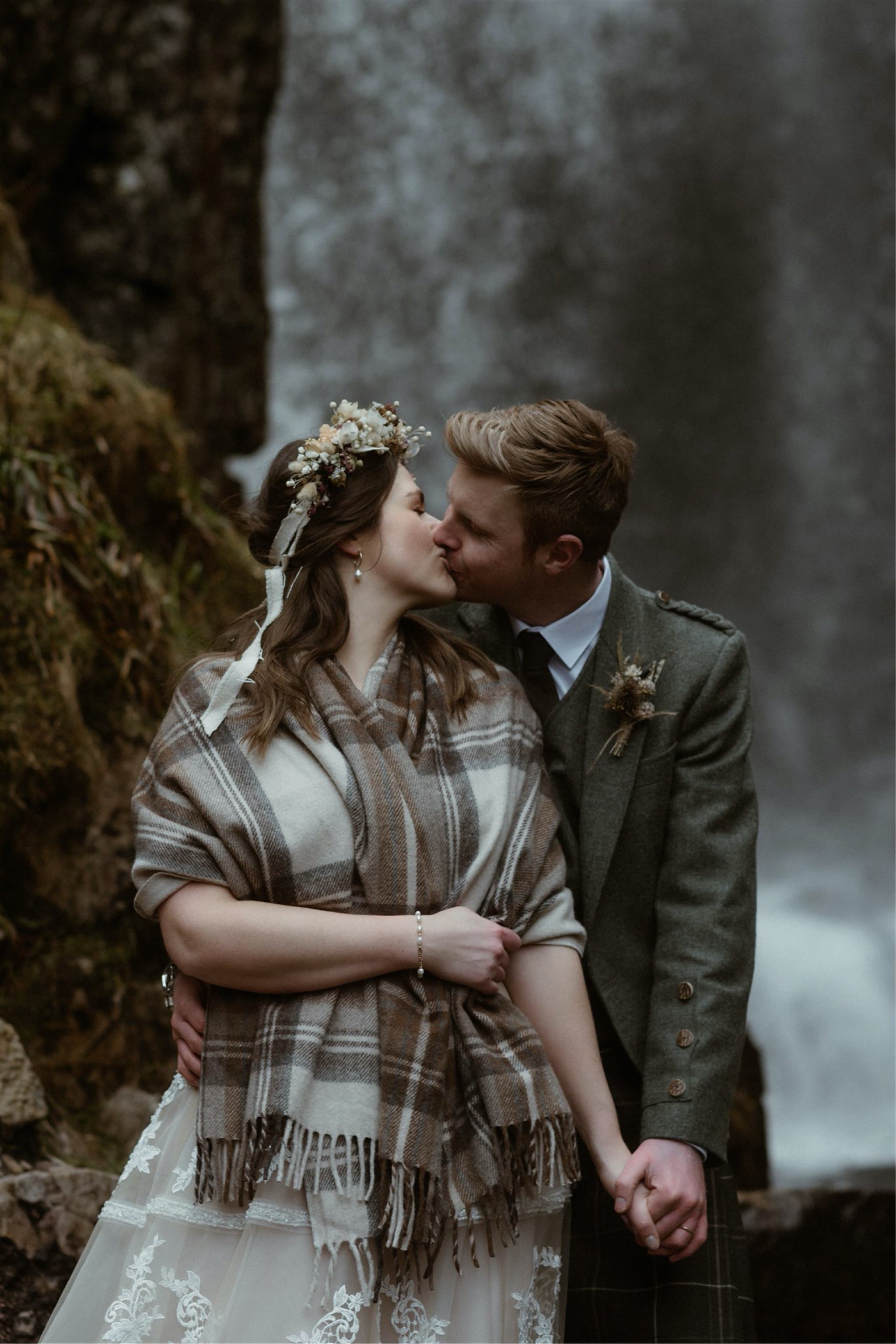 Bride and groom kiss in front of a waterfall after their Scottish elopement wedding in Assynt