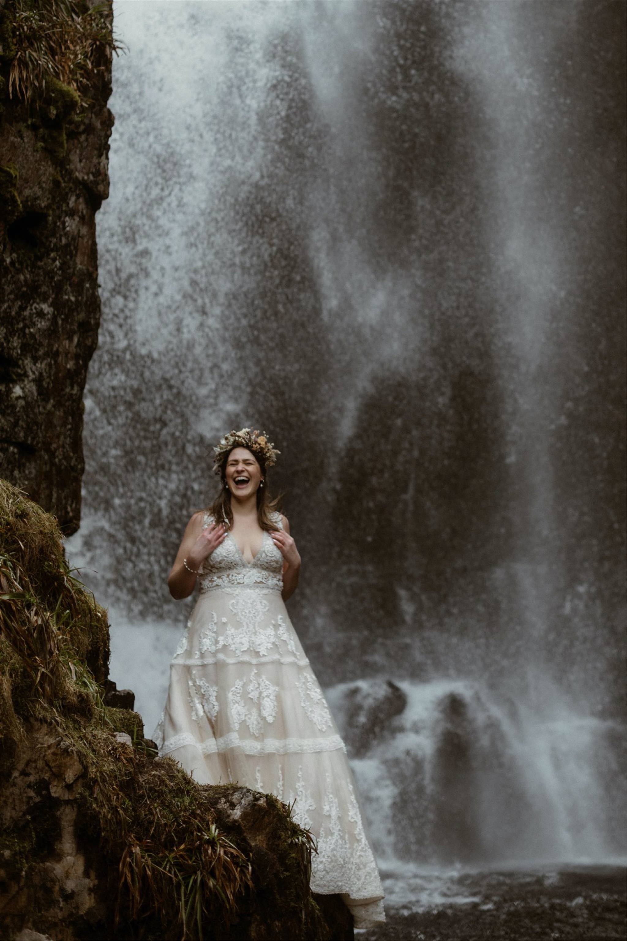 Bride standing in front of a waterfall and laughing after her elopement in Scotland