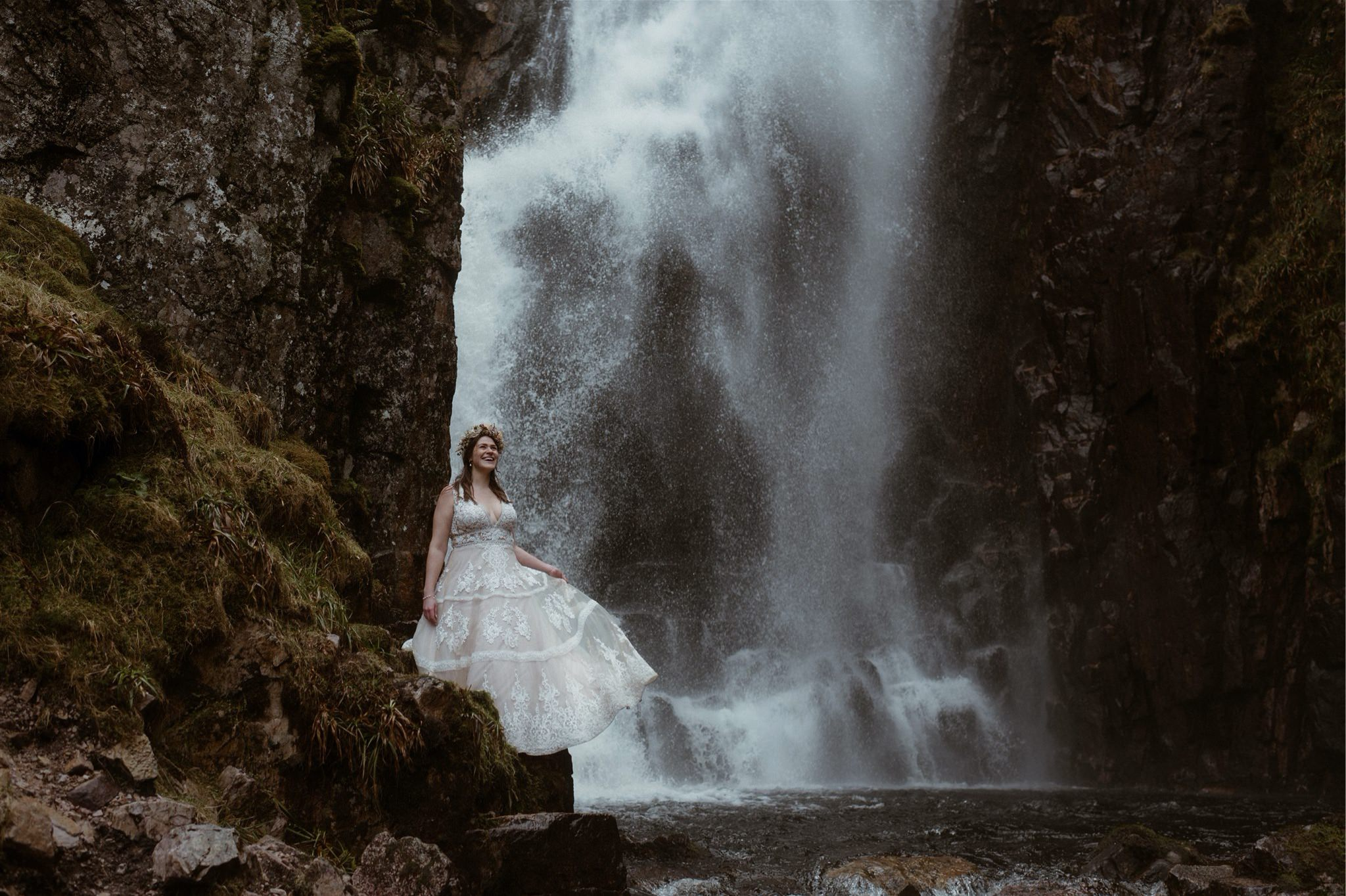 Bride standing in front of a waterfall after her Scotland elopement wedding