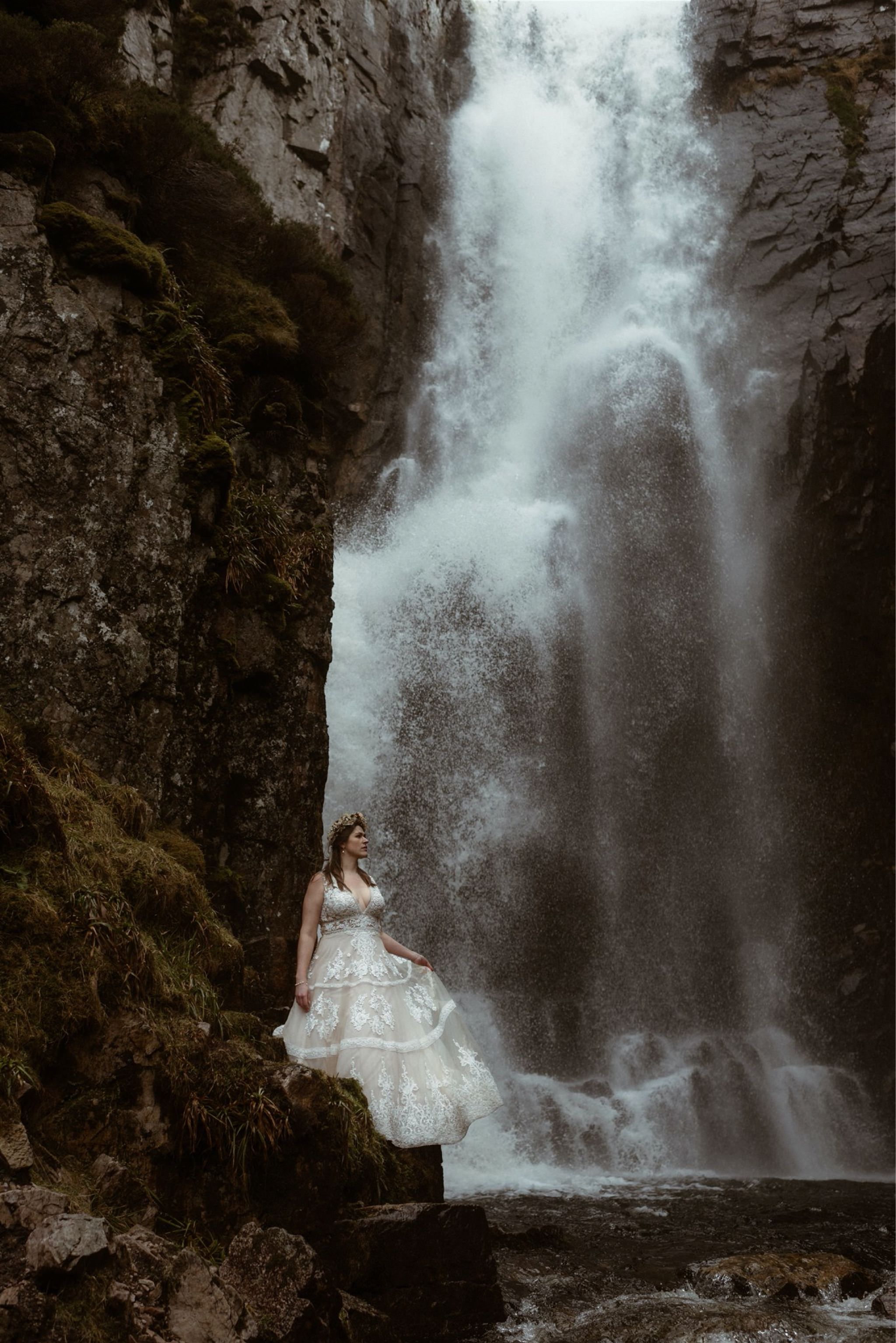 Bride standing in front of a waterfall after eloping in Scotland with The Carrels Photography