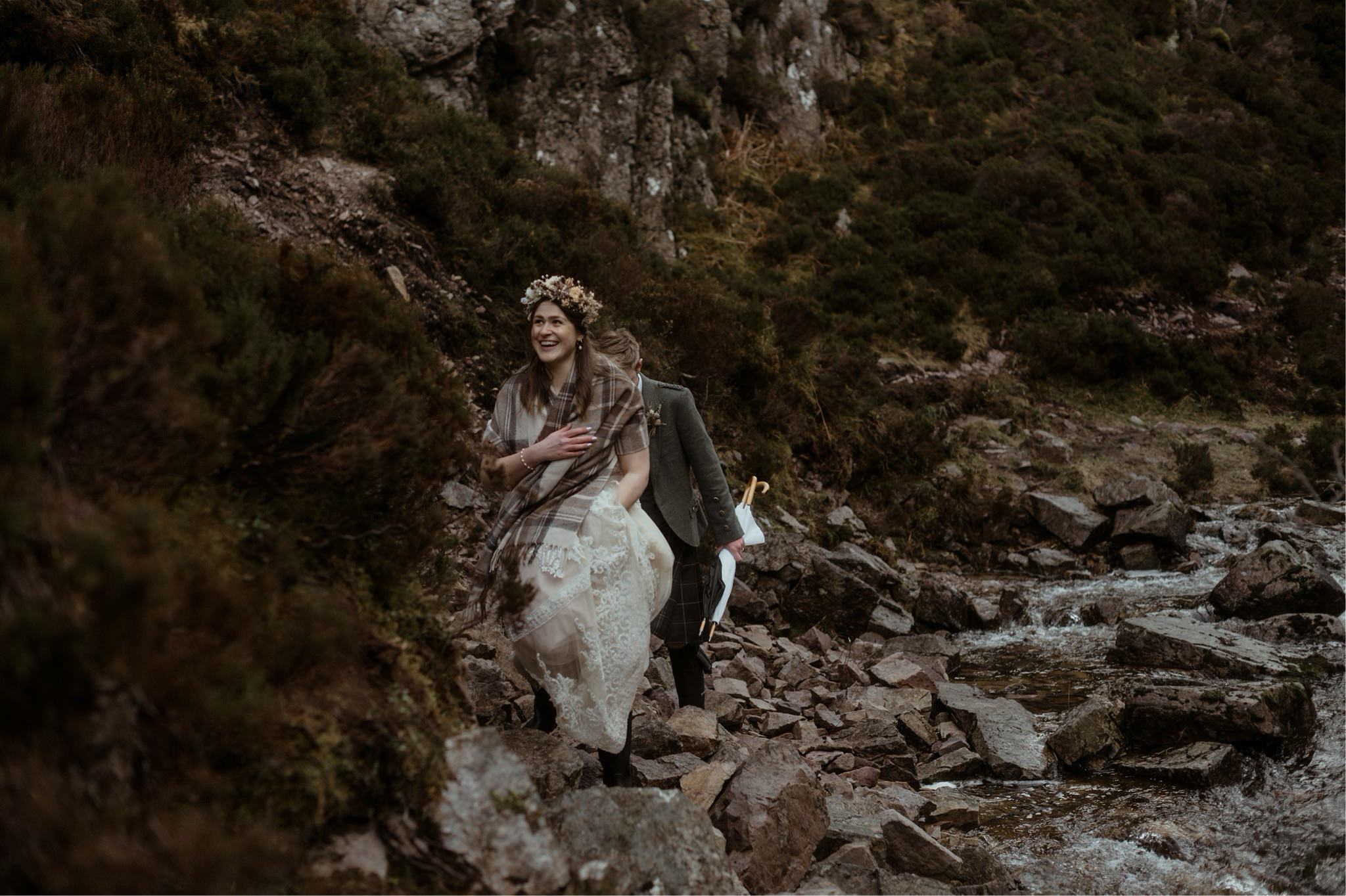 Bride and groom walking through a gorge in Assynt after a Scottish elopement wedding