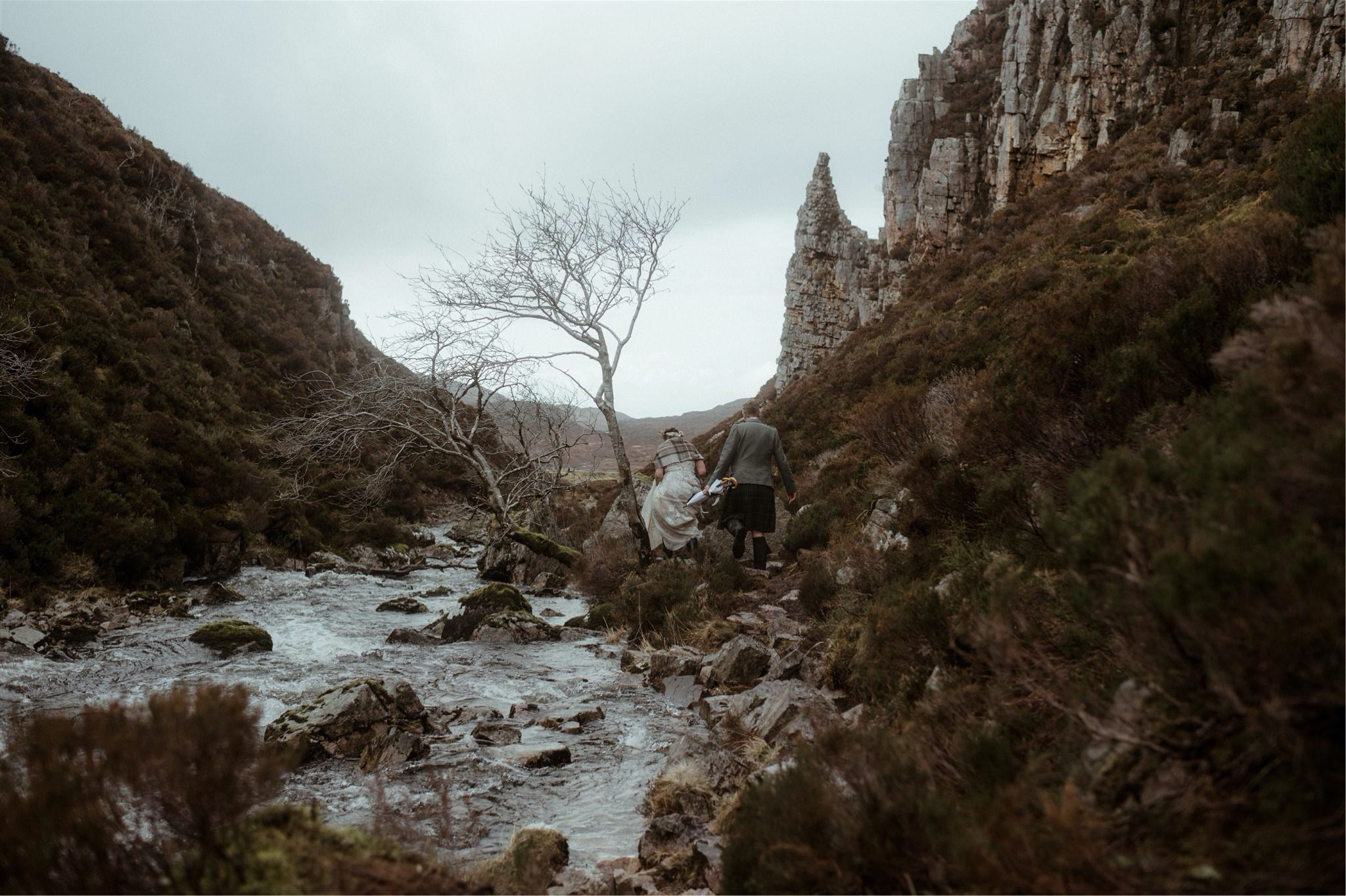 Bride and groom walking through a gorge in Assynt after an elopement wedding in Scotland