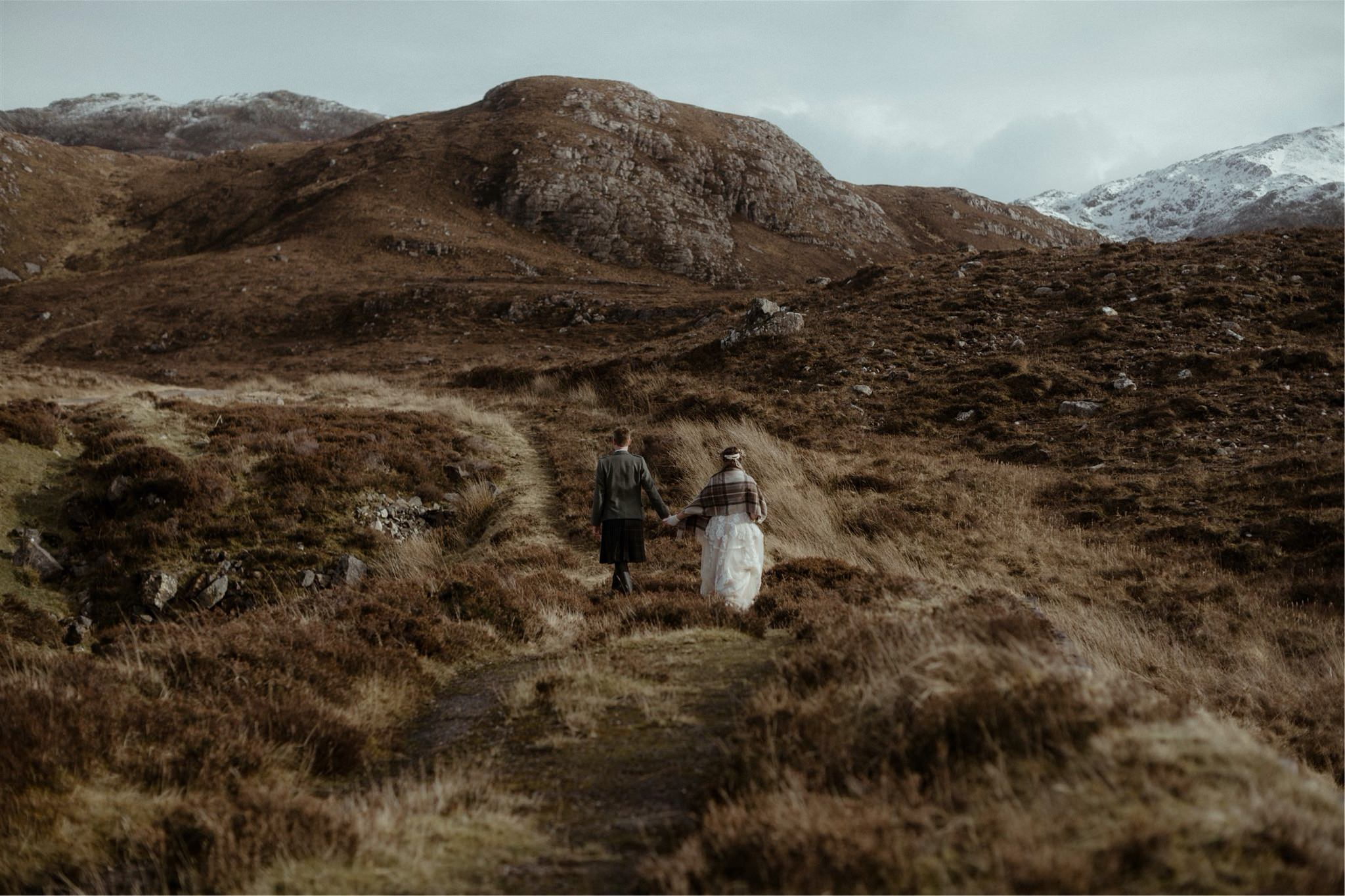 Bride and groom holding hands against a mountain backdrop during a Scotland elopement wedding