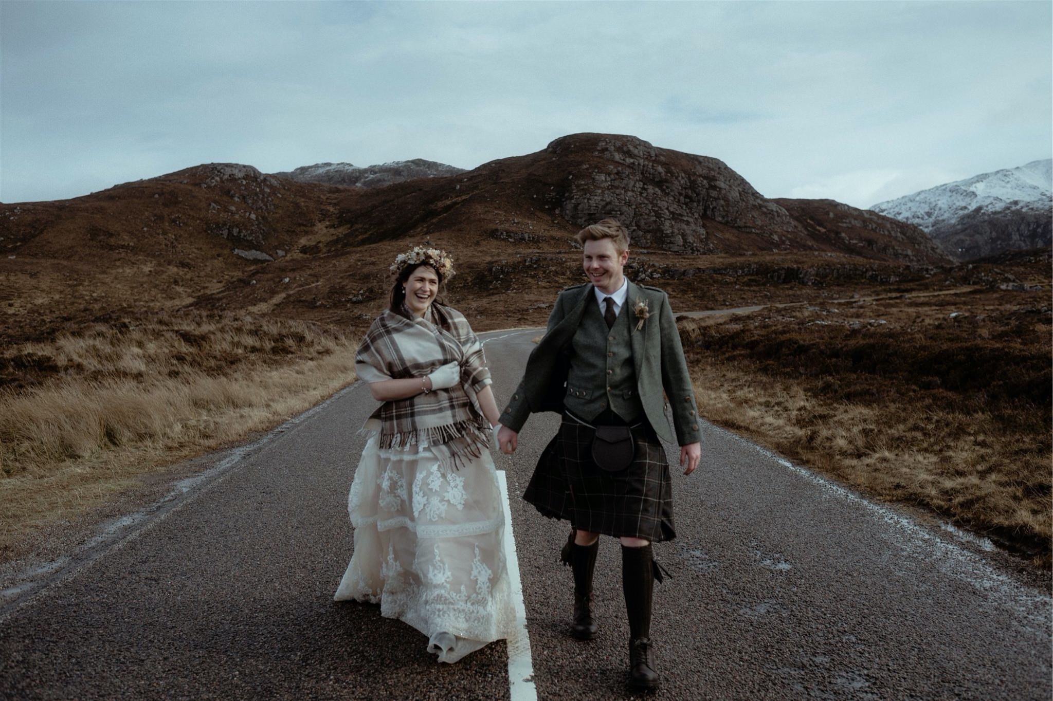 Bride and groom walking up a road in Assynt after a Scottish elopement wedding