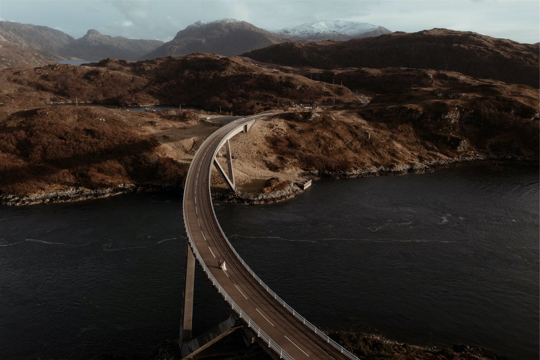 Drone shot of a bride and groom walking over a bride over a river in Assynt, Scotland