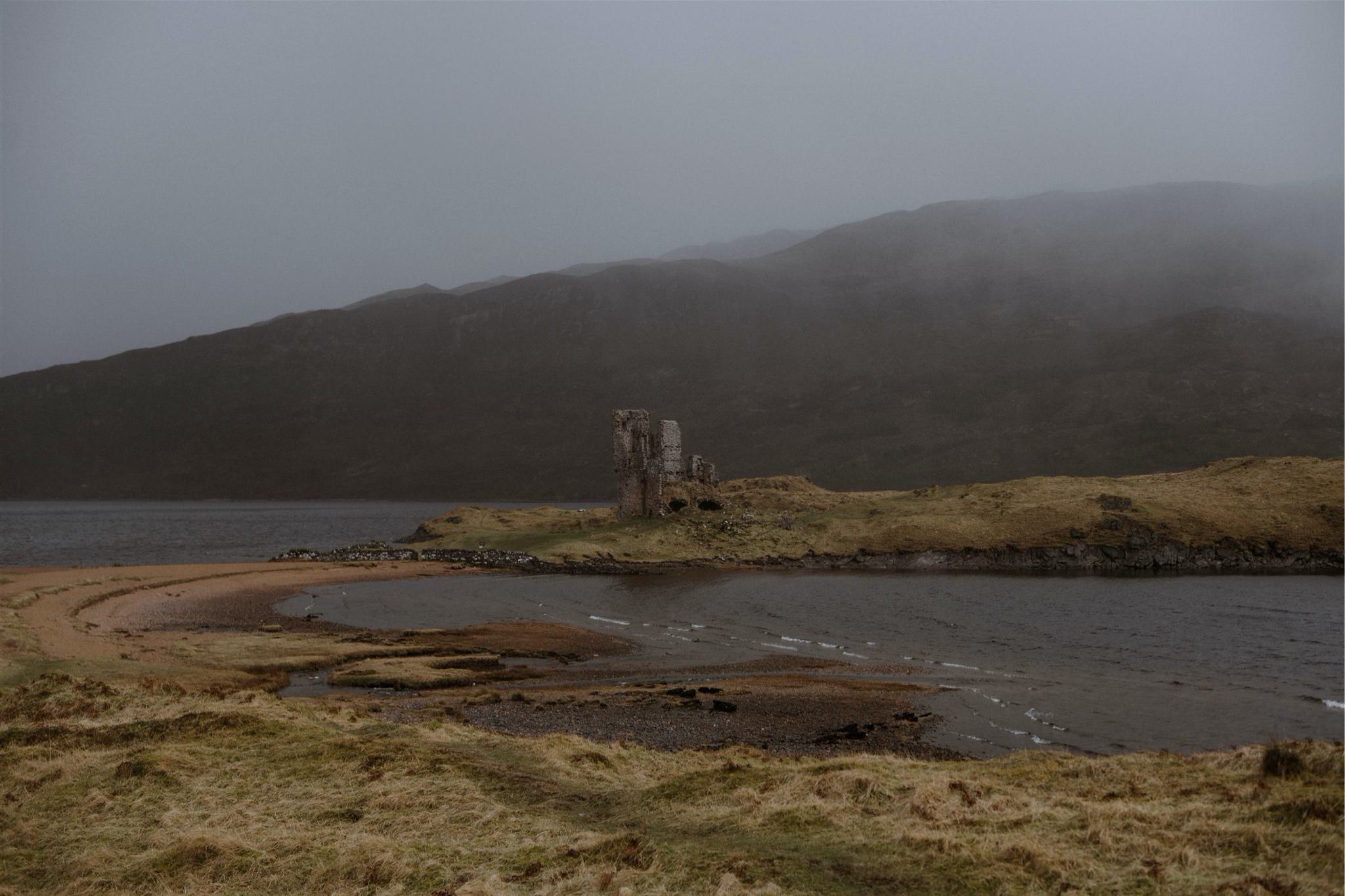 Landscape shot of a castle, sea and mountain in Assynt, Scotland