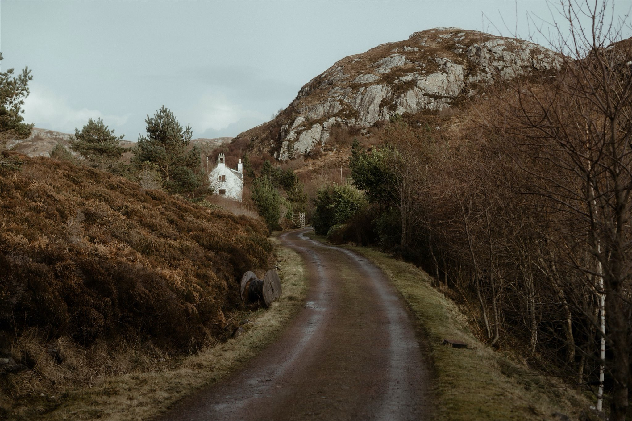 Landscape shot of aroad leading towards a cottage in Assynt, Scotland