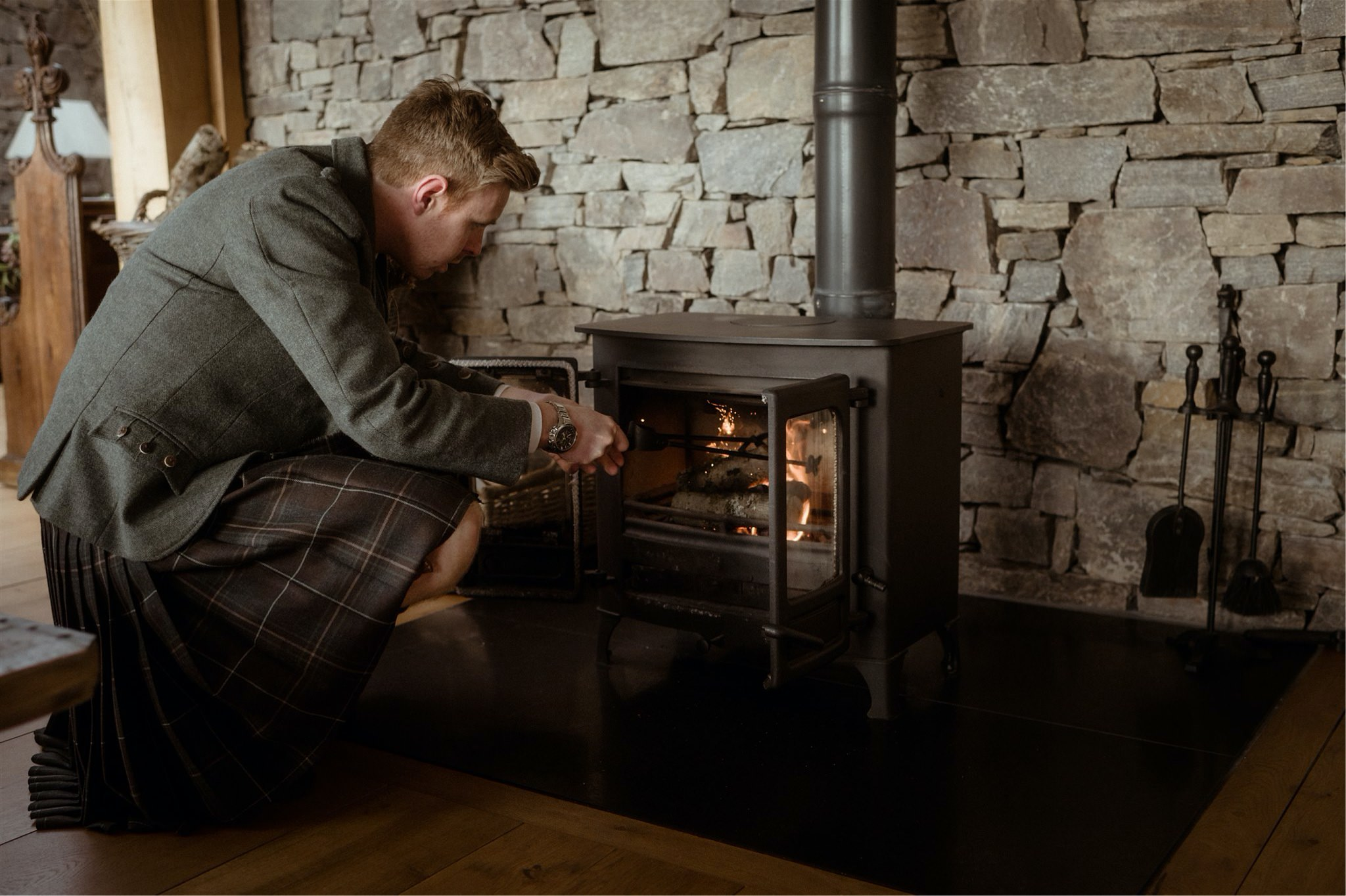 Groom stocking a fire in a cottage during a Scotland elopement wedding