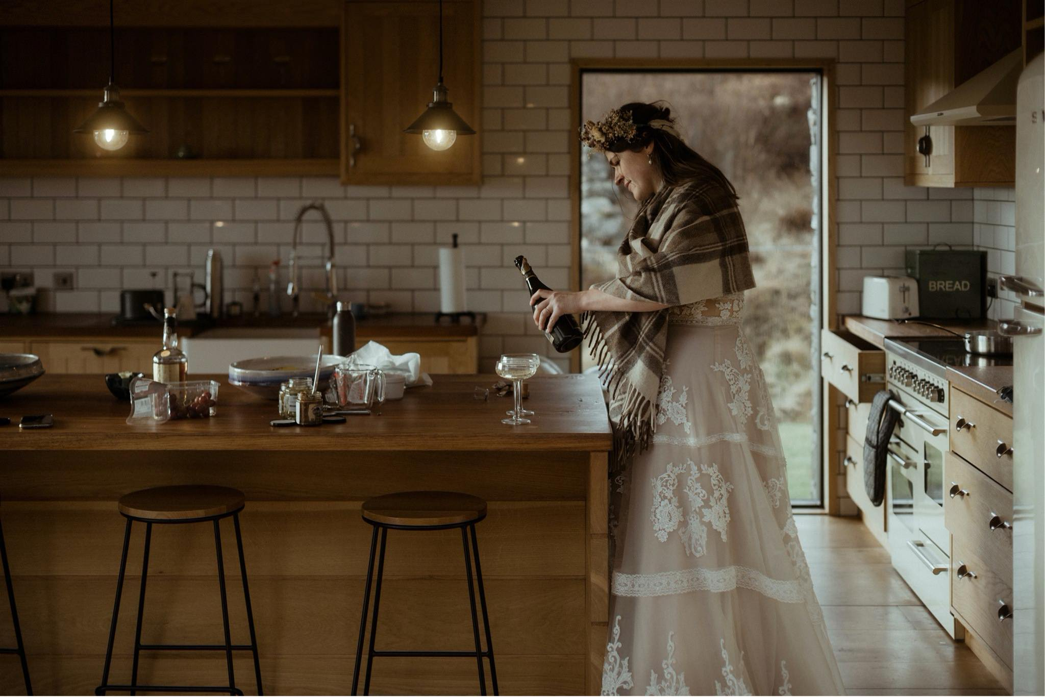 Bride pouring champagne in a cottage during an elopement in Scotland