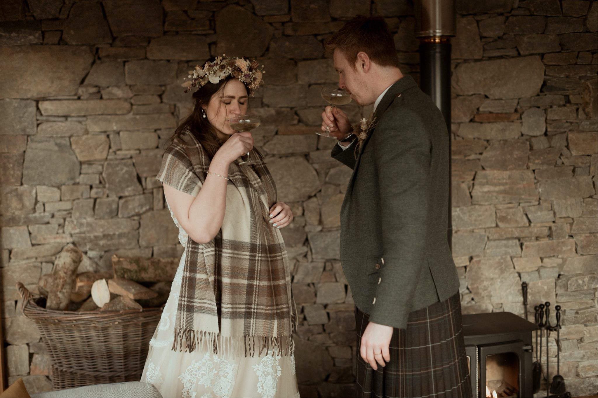 Bride and groom drink champagne in a cottage after their elopement in Scotland