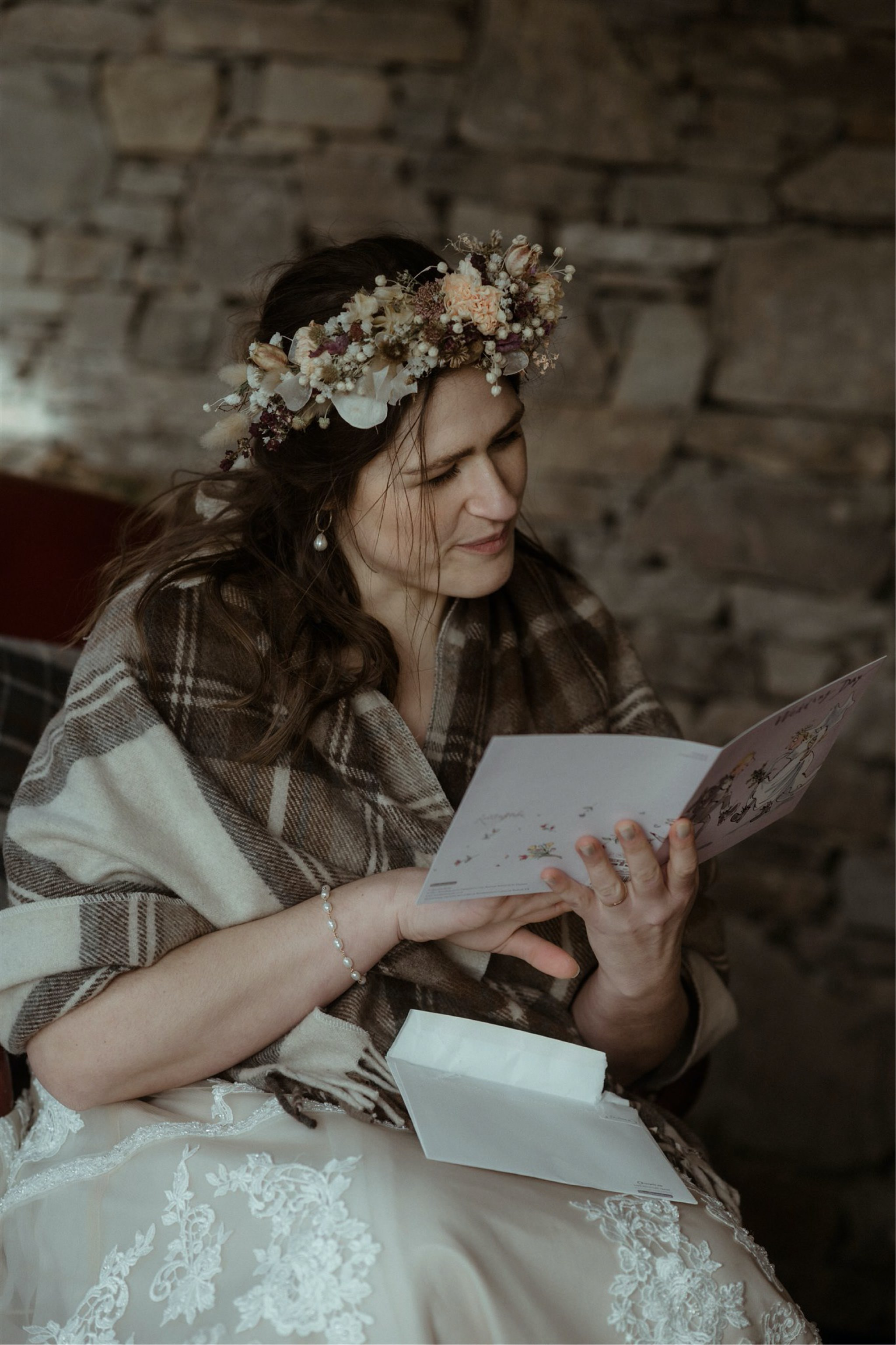 Bride reading cards in a cottage after a Scottish elopement wedding