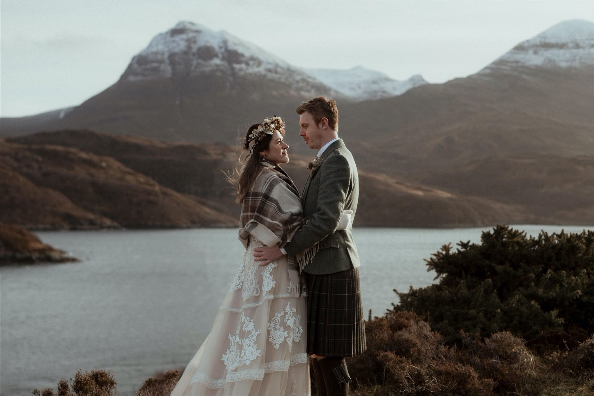 Bride and groom embrace in front of the mountains after their Scottish elopement wedding in Assynt