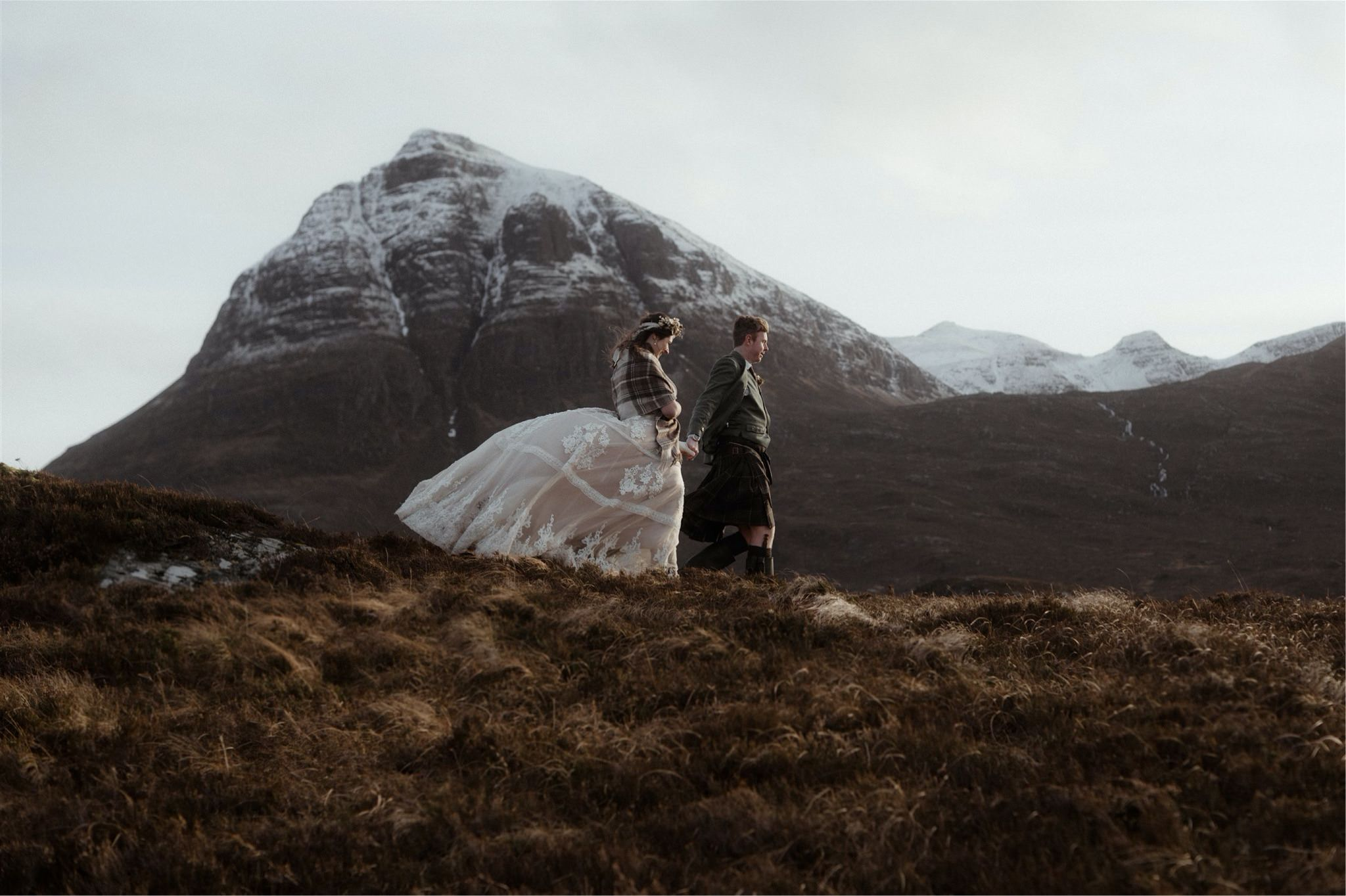 Bride and groom walking in the mountains after eloping in Scotland
