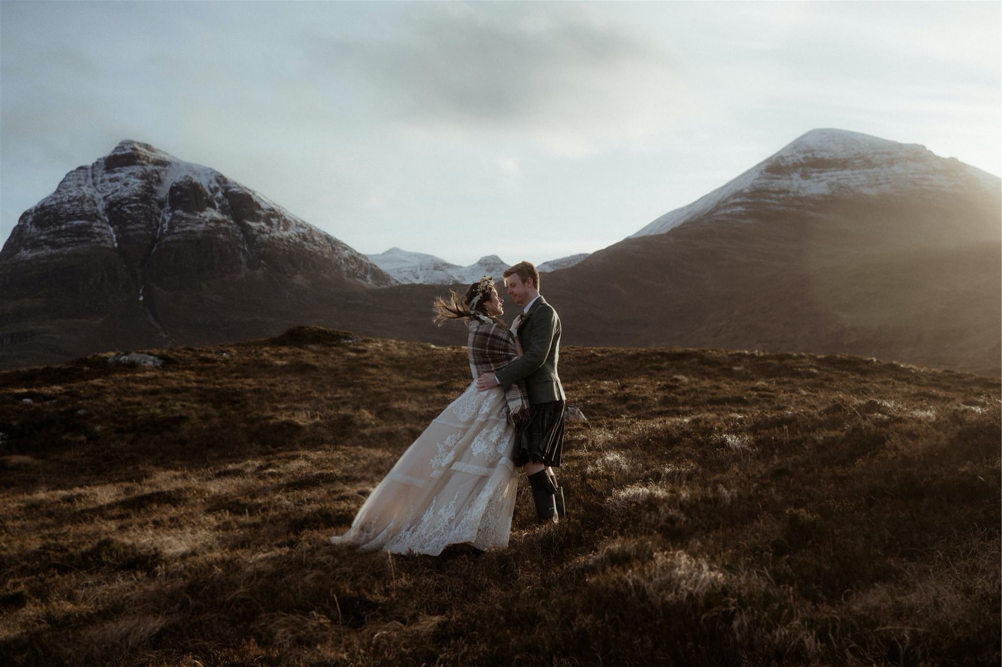 Bride and groomembrace in the mountains after their Scotland elopement wedding in Assynt