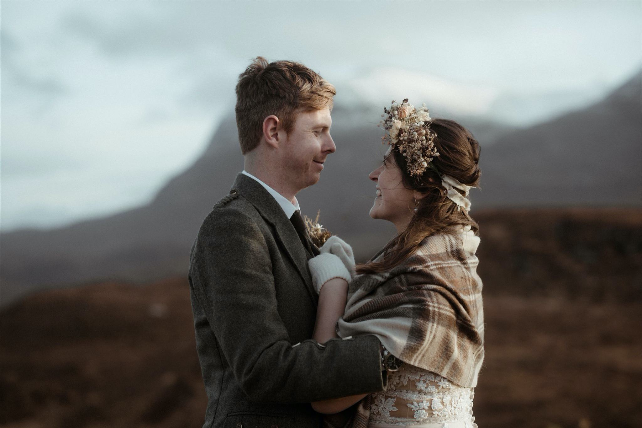 Bride and groom embrace in the mountains after eloping in Scotland in Assynt
