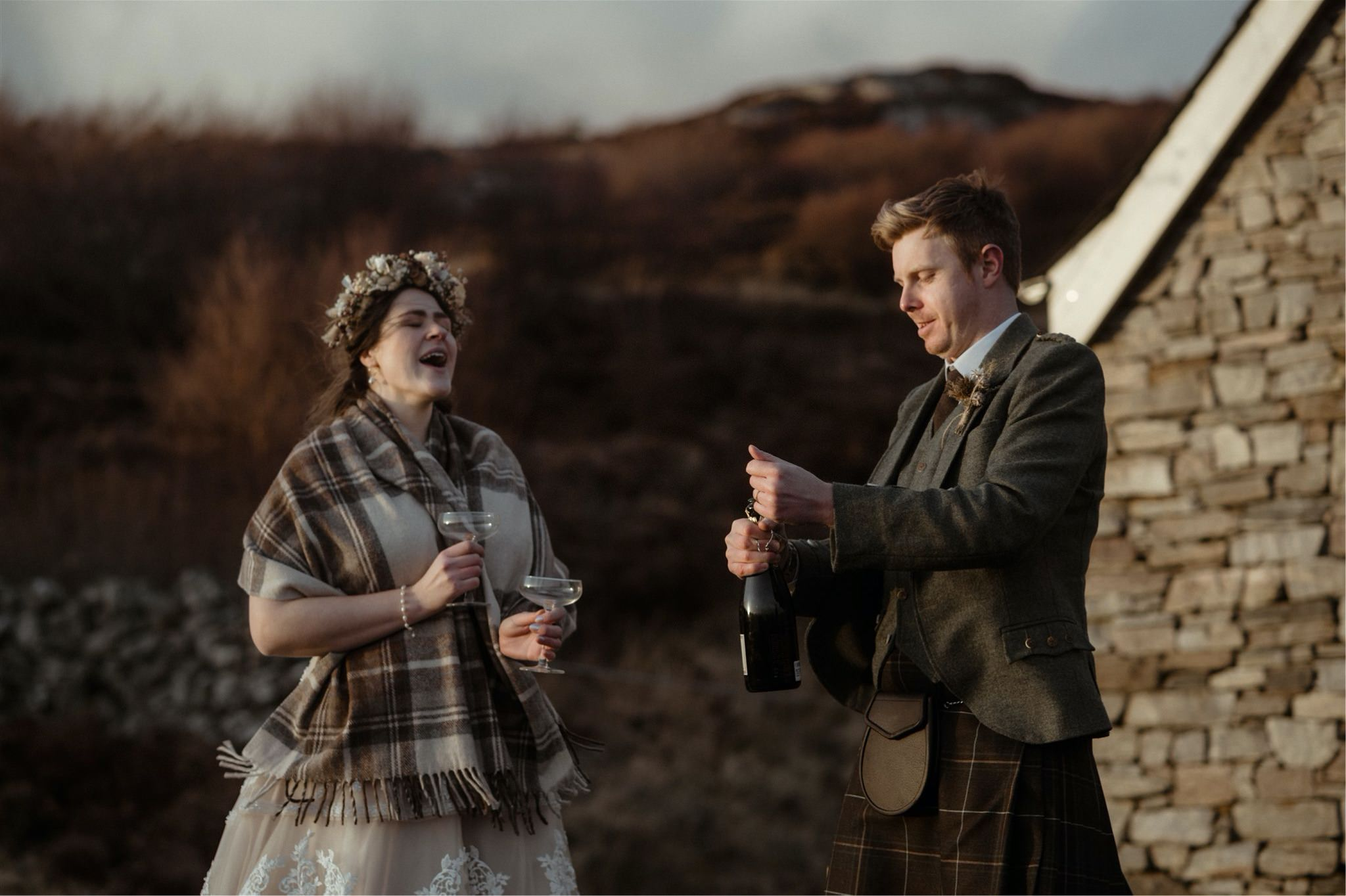Bride and groom open a bottle of Champagne outside their cottage after their elopement in Scotland