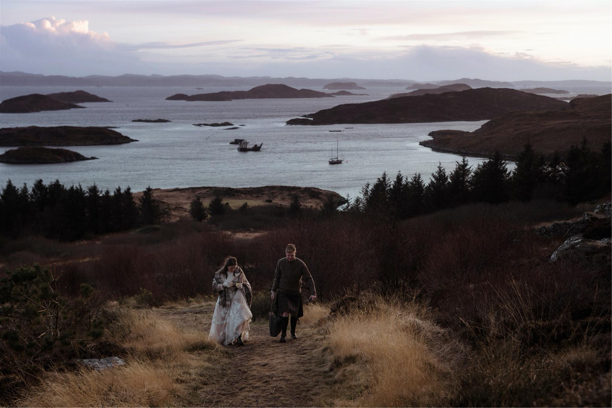 Bride and groom walking up hillside at sunset after an elopement wedding in Scotland