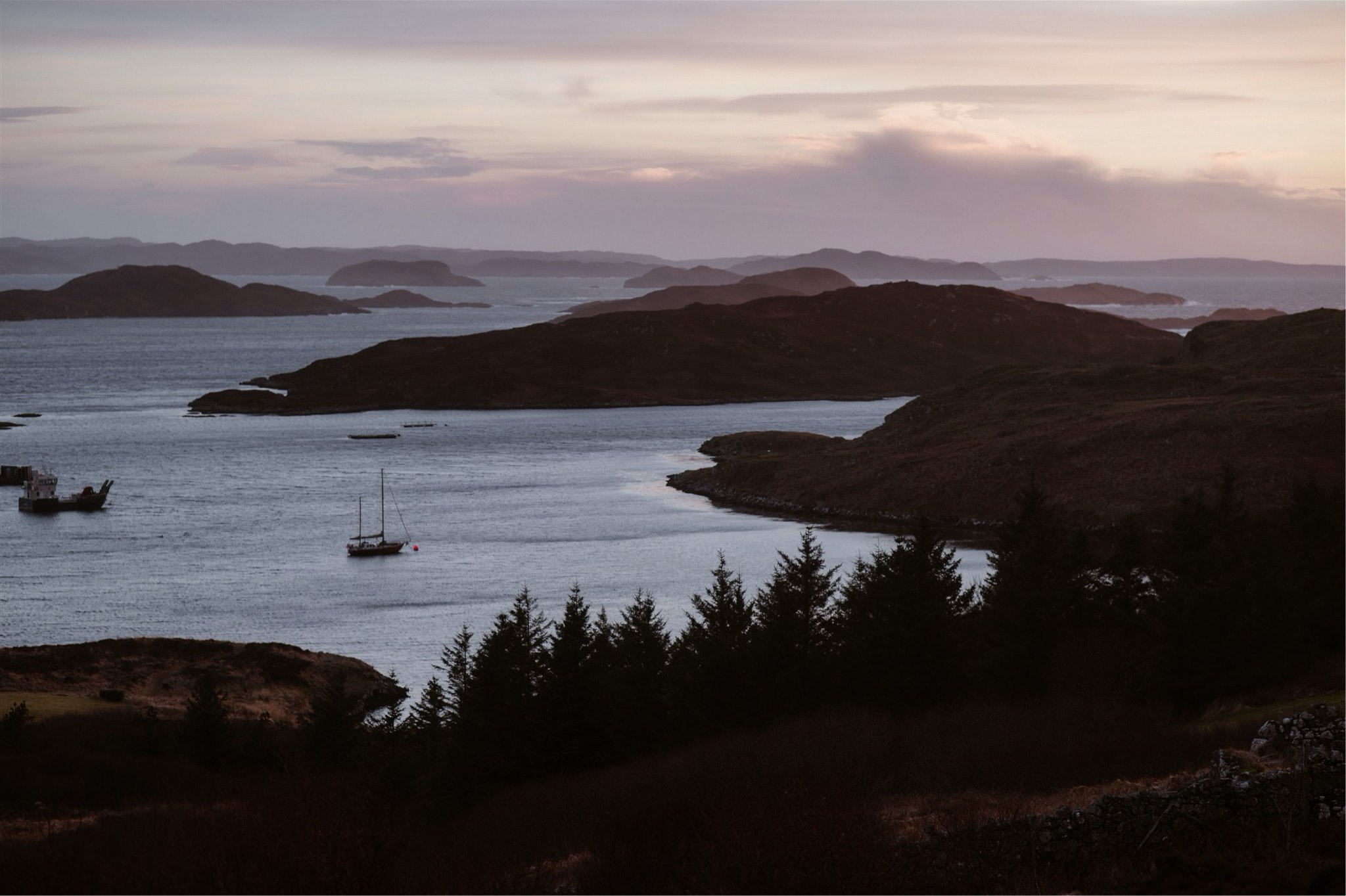 Sea views with boats at sunset in Assynt, Scotland - on the North Coast 500