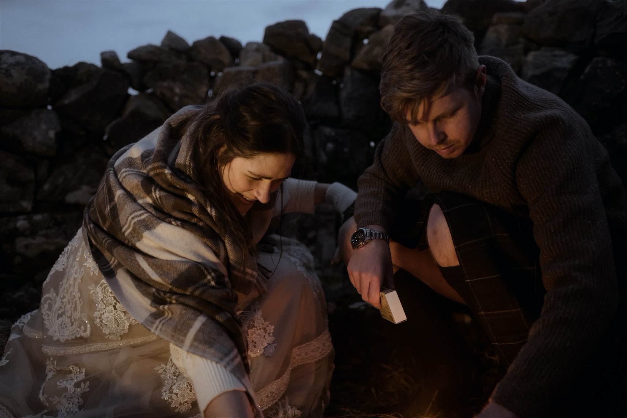 Bride and groom light a fire in a cairn after their Scotland elopement wedding