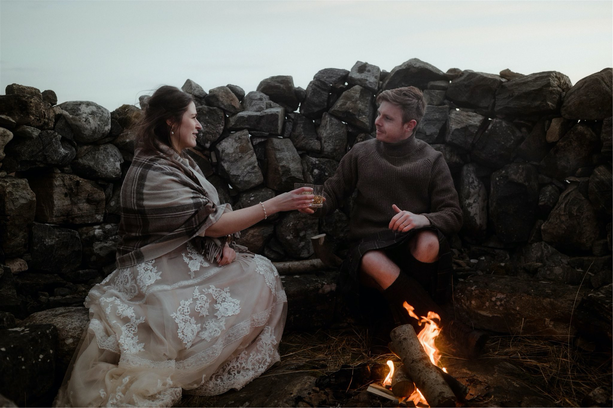 Bride and groom toast each other but he fire in a cairn after their Scottish elopement wedding